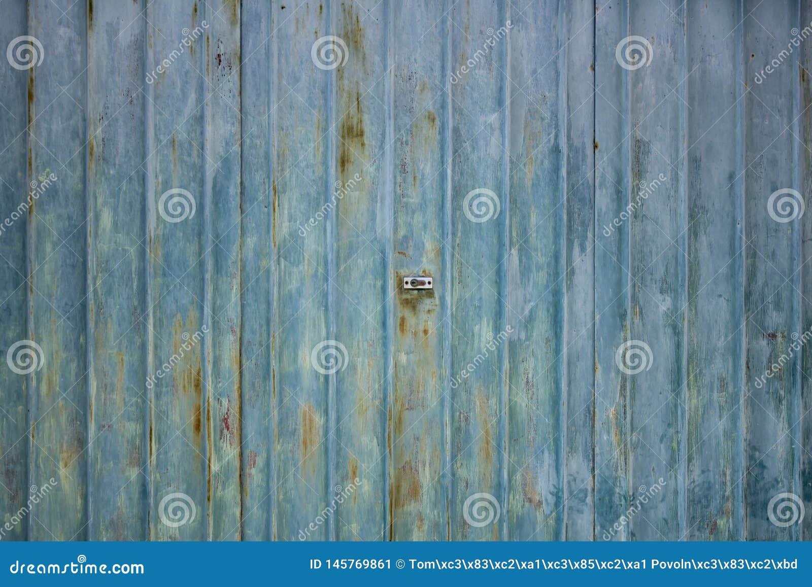 Textura oxidada acanalada de las puertas del garaje del metal con la cerradura en el centro