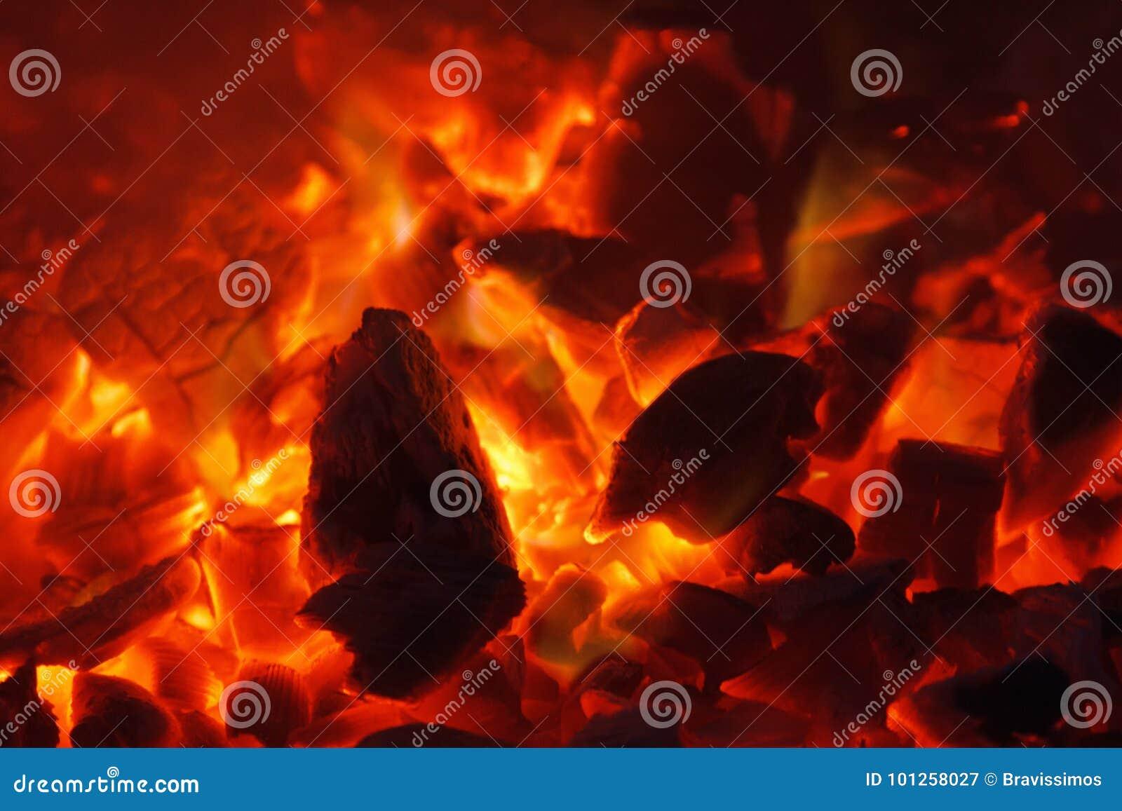 Textura quente de incandescência do fundo do close-up dos carvões amassados do carvão vegetal bonfire