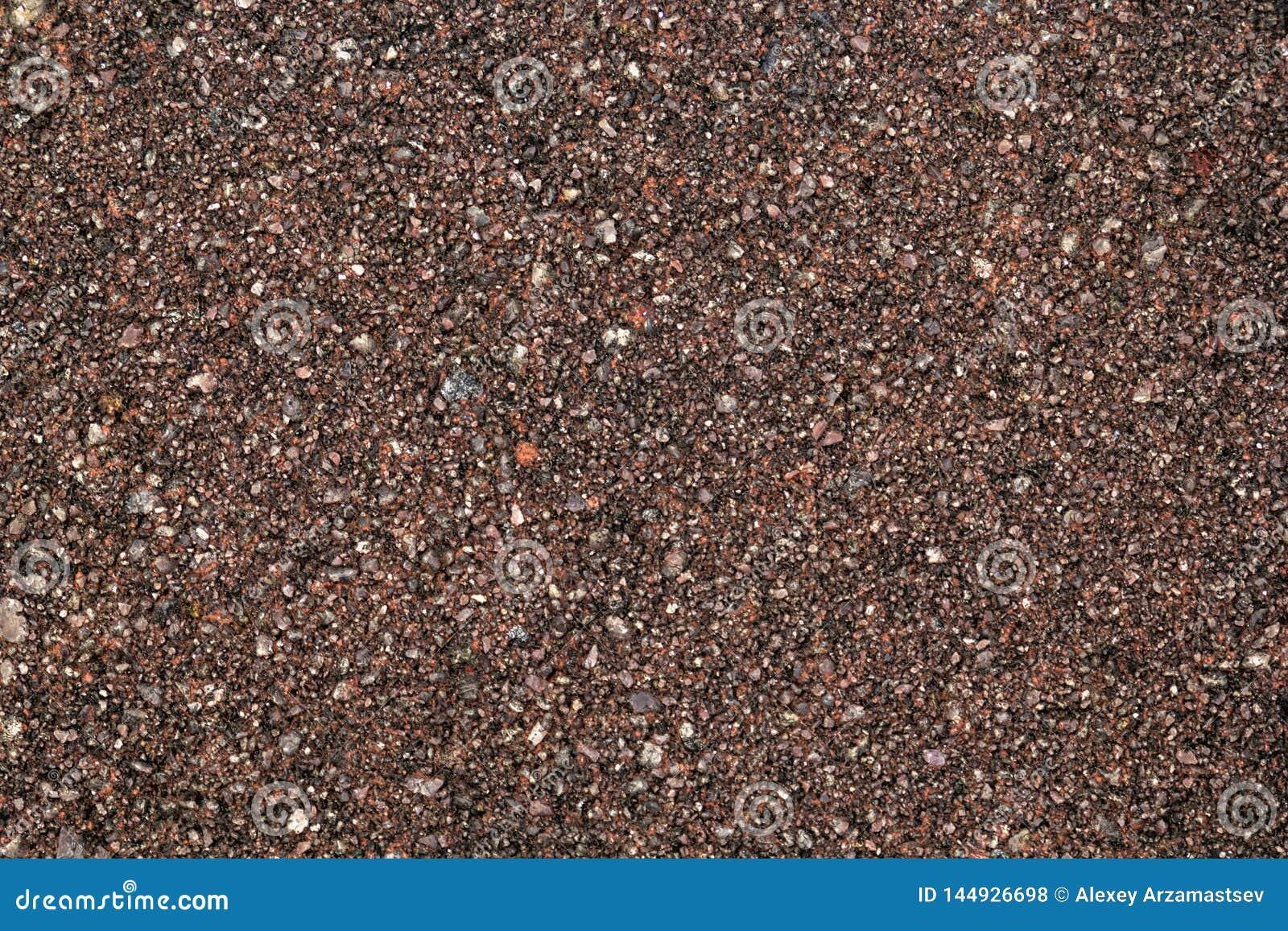 Texture du sable brut avec les puces en pierre rouges