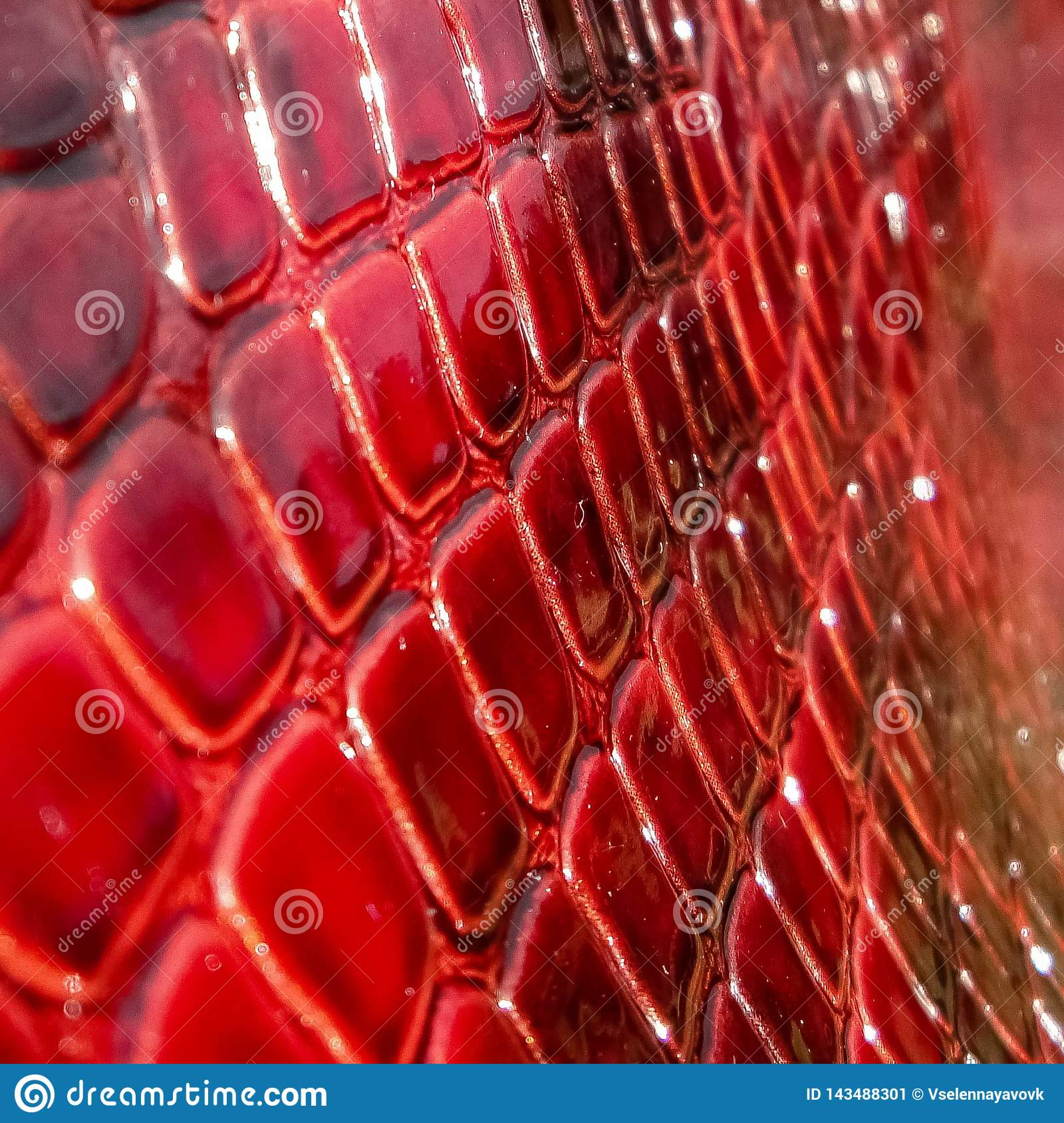 Texture of genuine patent leather close-up, embossed under the skin a red, pink reptile.