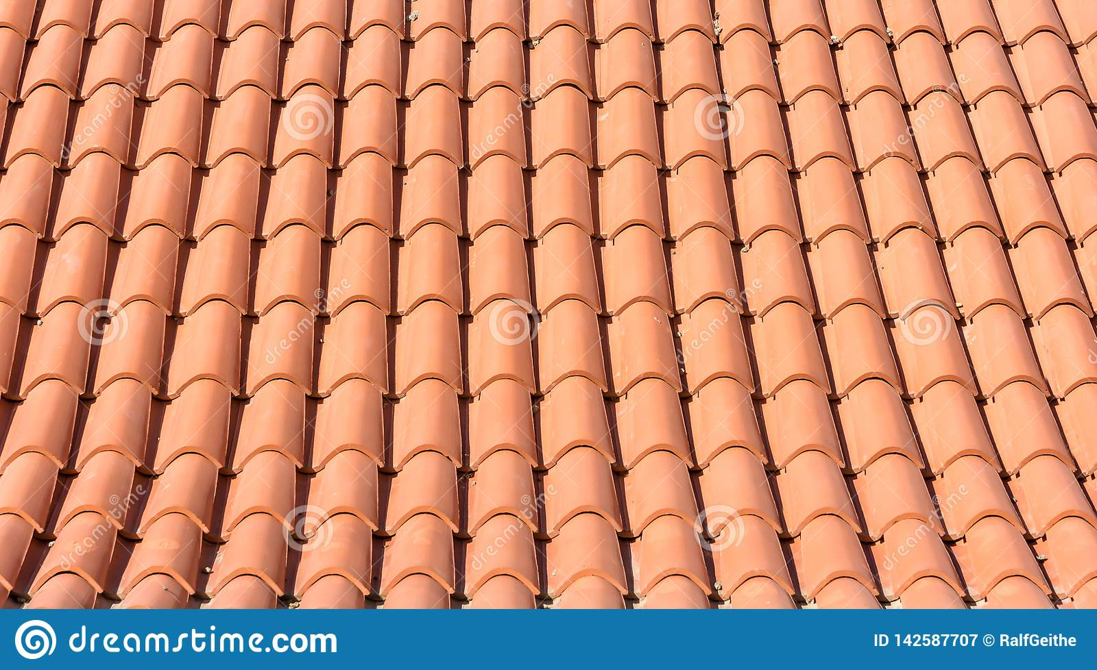 Texture of orange roof tiles of a new roof