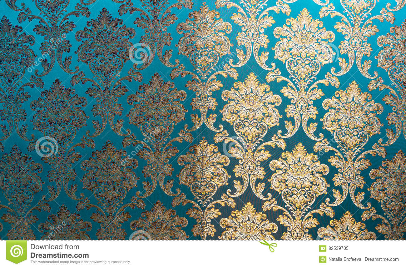 The texture of silk with a floral pattern. Chinese silk brocade, beautiful expensive fabric background. Gold ornament turquoise em