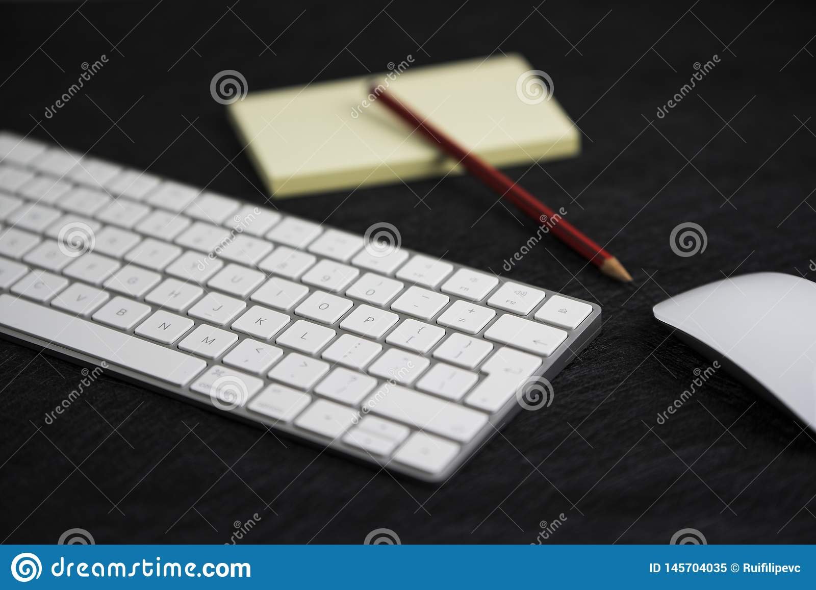 Textured black board with a pencil on a paper, a keyboard and a mouse