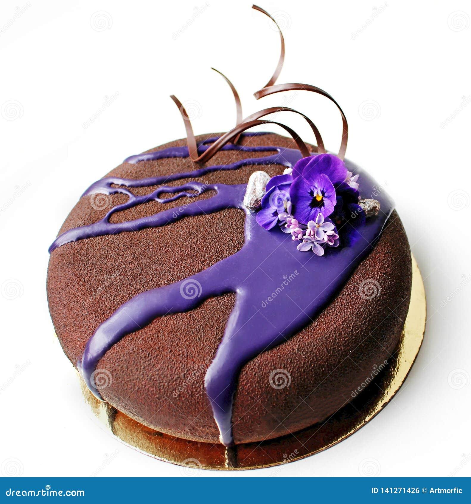 Dark chocolate cake with purple mirror glaze and spring flowers