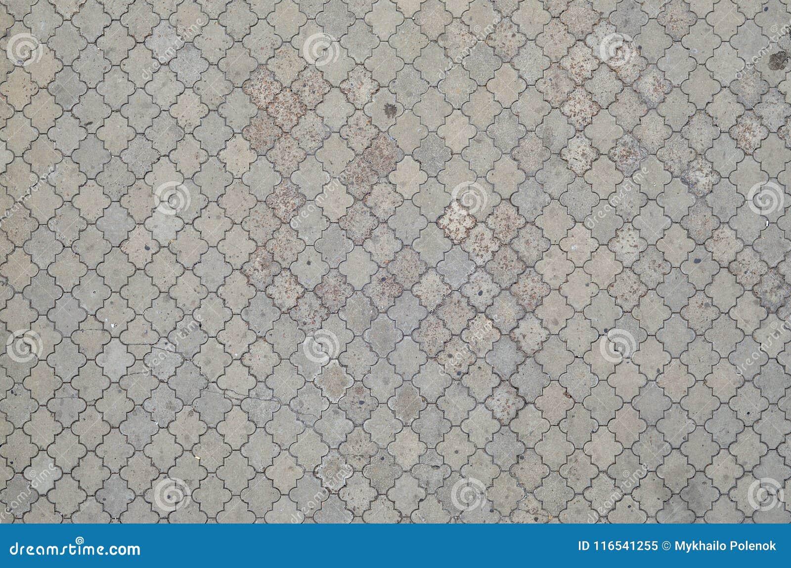 Texturen av en rytmisk mosaik som göras av konkreta tegelplattor Bakgrundsbild av ett stort område av den gamla och skadade grå f