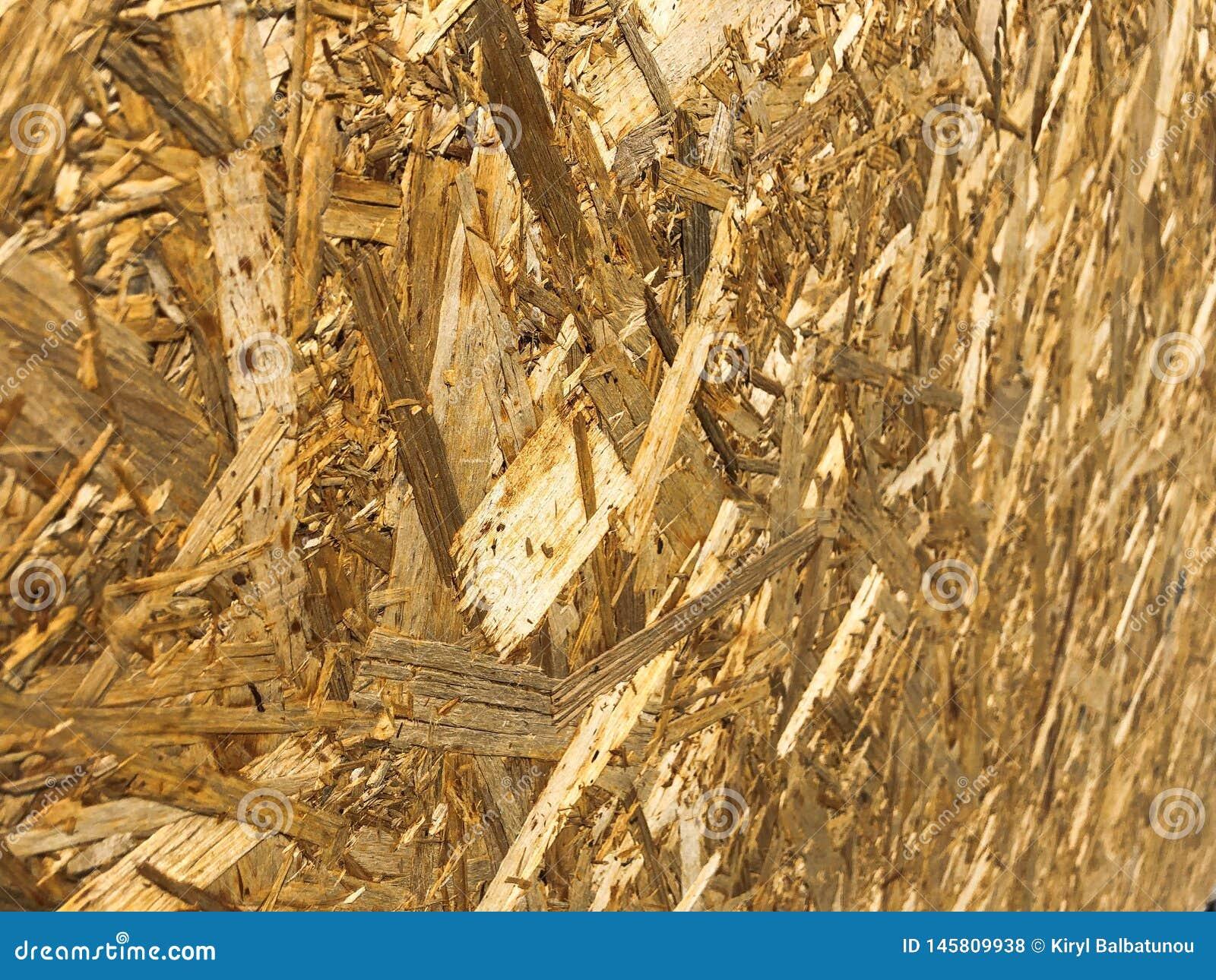 Texturen vanuit een invalshoek van houten geel bouwmateriaal van spaanders en samengeperst zaagsel OSB, het afval van de meubilai