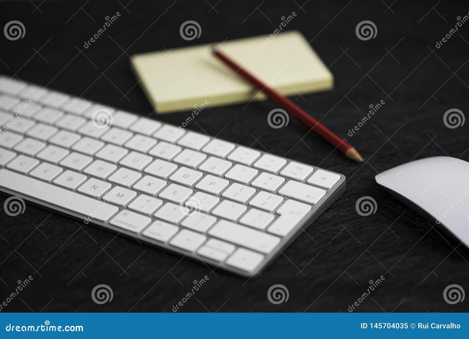 Texturerat svart bräde med en blyertspenna på ett papper, ett tangentbord och en mus