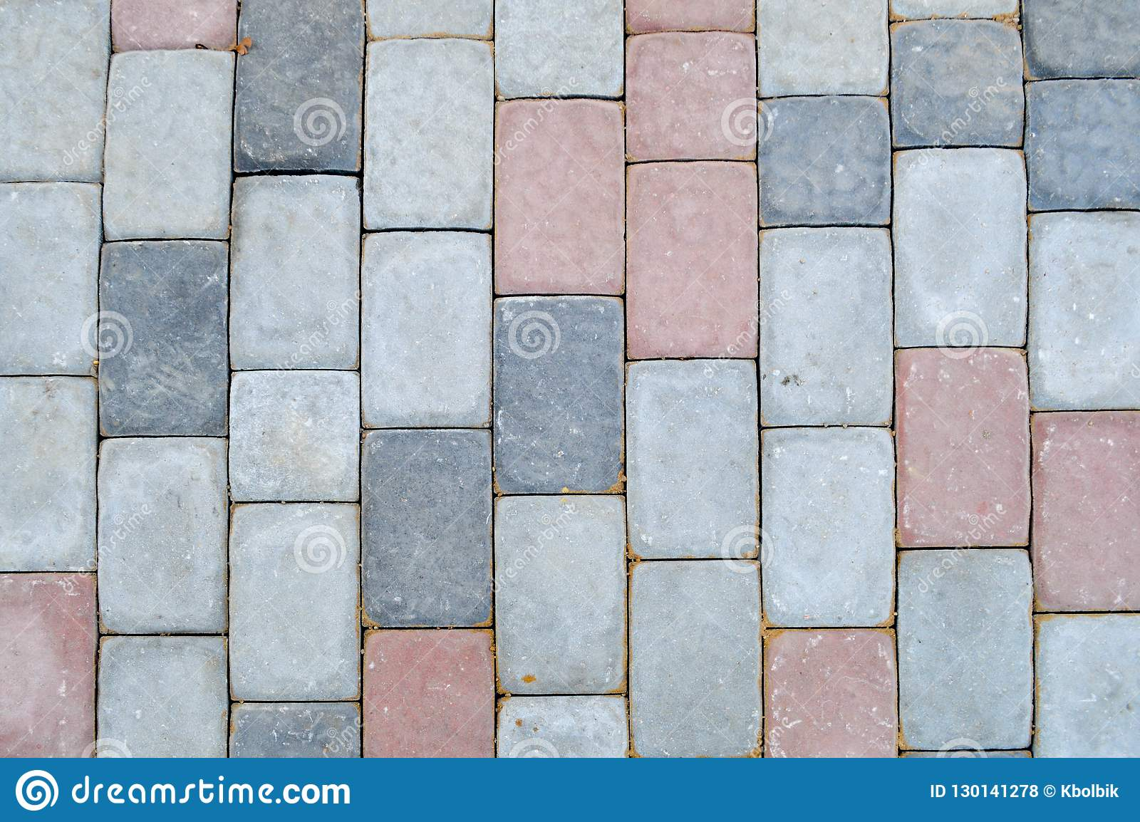Textuur van grijze rechthoekige concrete steen het bedekken plakken op de weg met naden De achtergrond