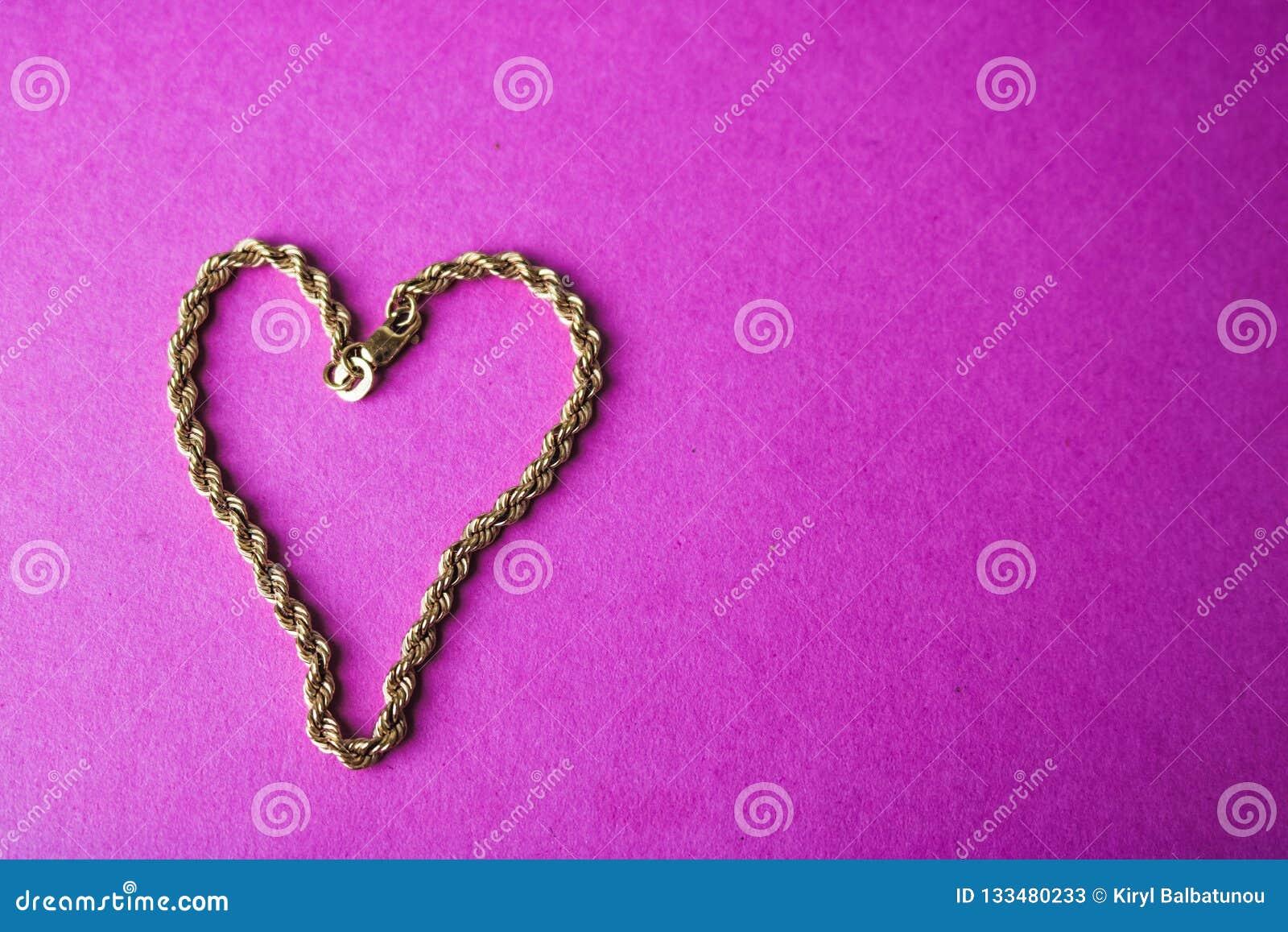 Textuur van het mooie gouden feestelijke ketting unieke weven in de vorm van een hart op een roze purpere ruimte als achtergrond