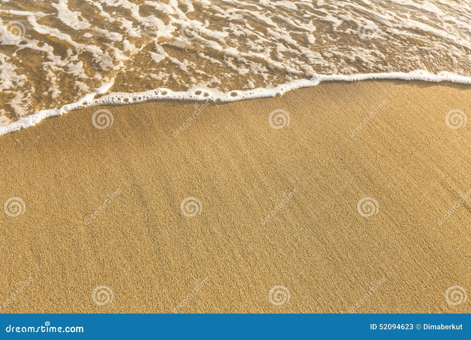 Textuur van strand overzees zand met een zachte golf van branding De zomer