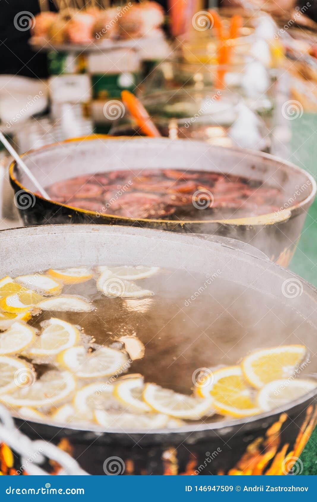 Thé chaud de fruit dans les pots sur les charbons