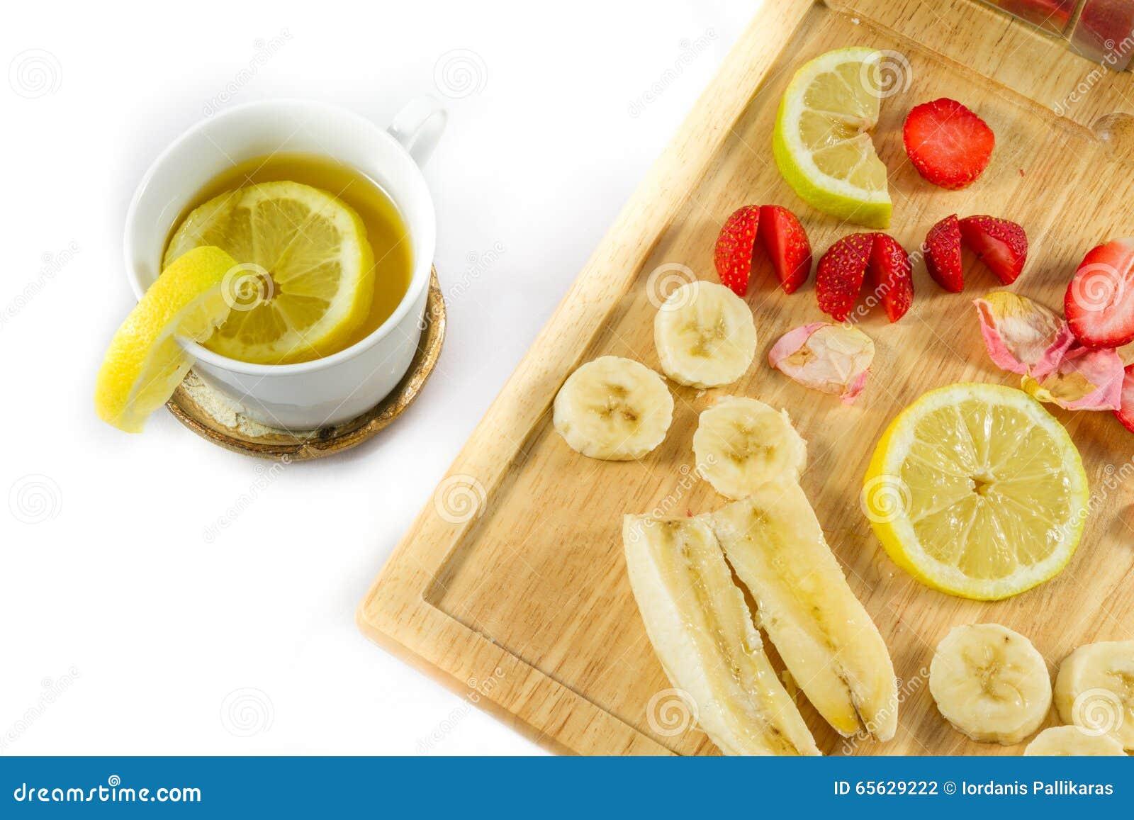 Thé de citron et citron, fraises et banane coupés en tranches sur le conseil en bois