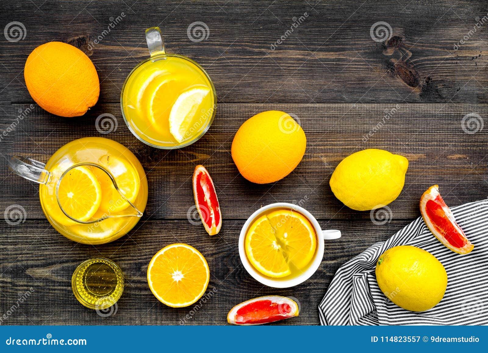 Thé de fruit La tasse de thé et la théière parmi l agrume sur la vue supérieure de fond en bois foncé copient l espace
