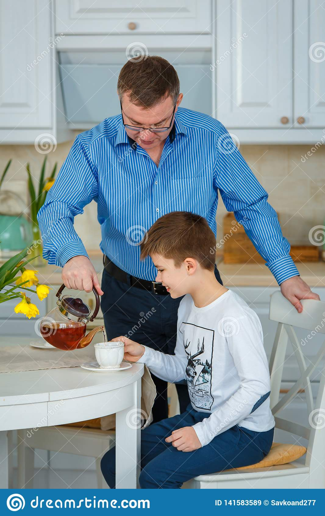 Thé de matin Le père verse le thé