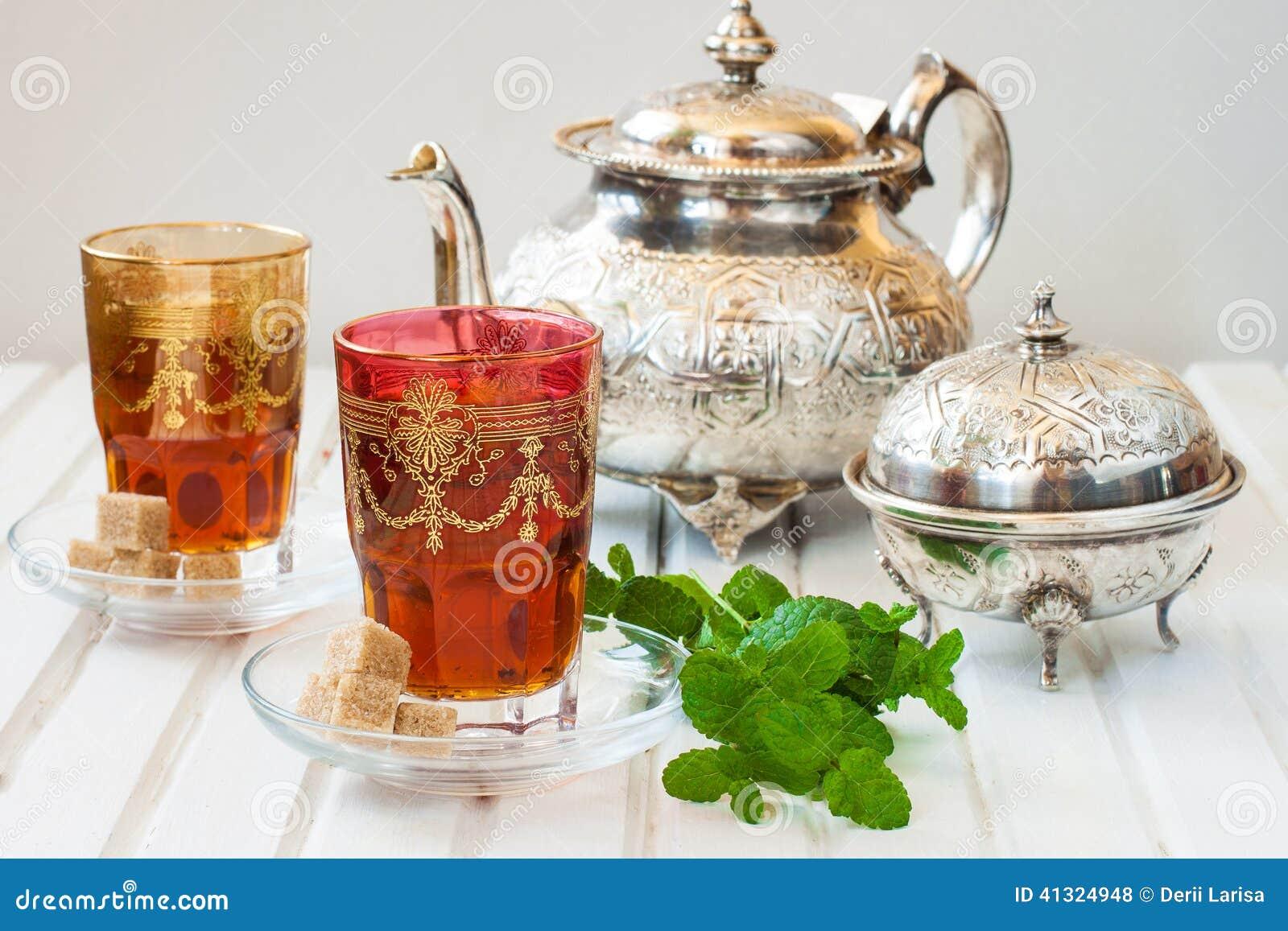 Th marocain avec la menthe et le sucre dans un verre sur for Table a the marocaine