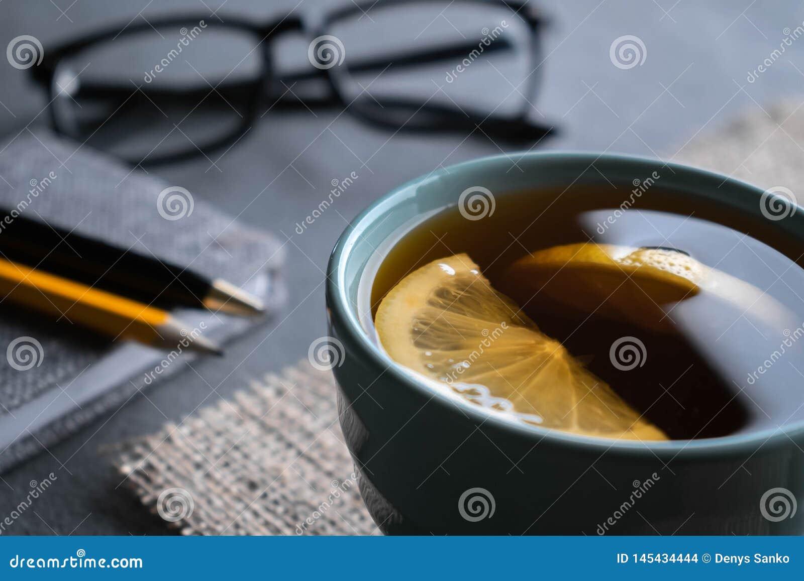 Thé noir avec des tranches de citron sur une serviette de toile de jute avec le stylo de bloc-notes, un crayon et des verres
