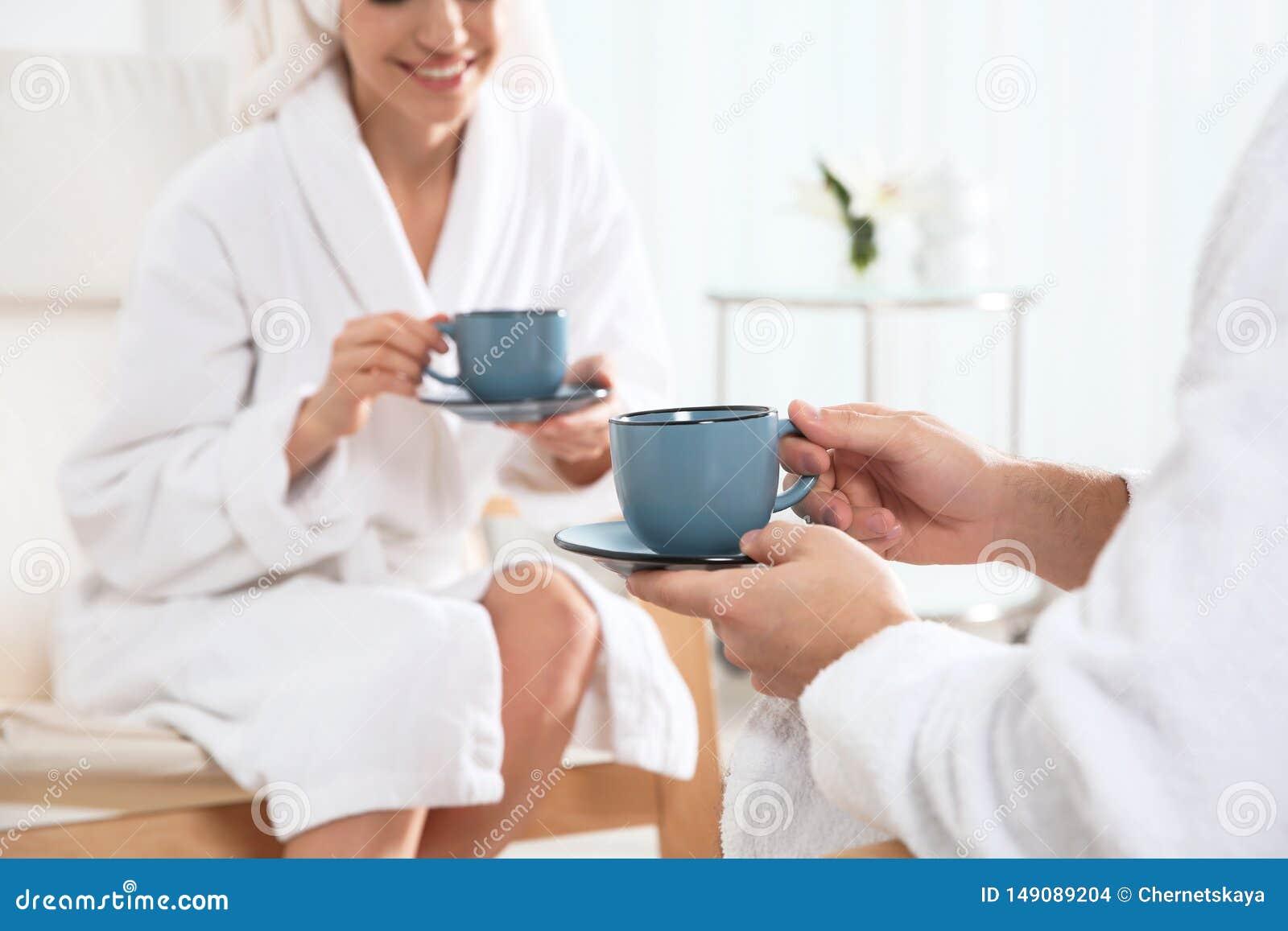 Thé potable de jeunes couples romantiques dans le salon de station thermale