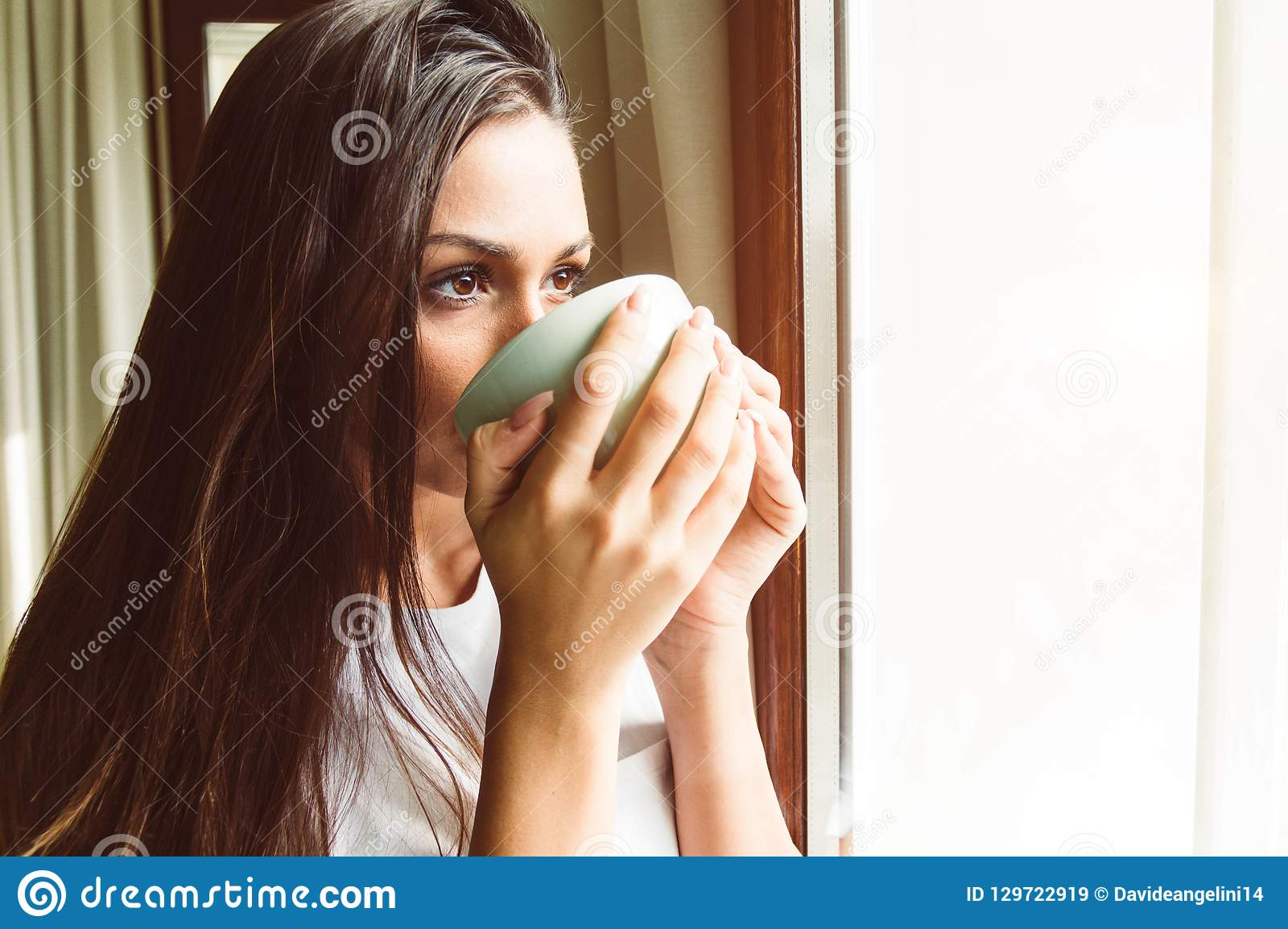 Thé potable de pensée de femme à la fenêtre