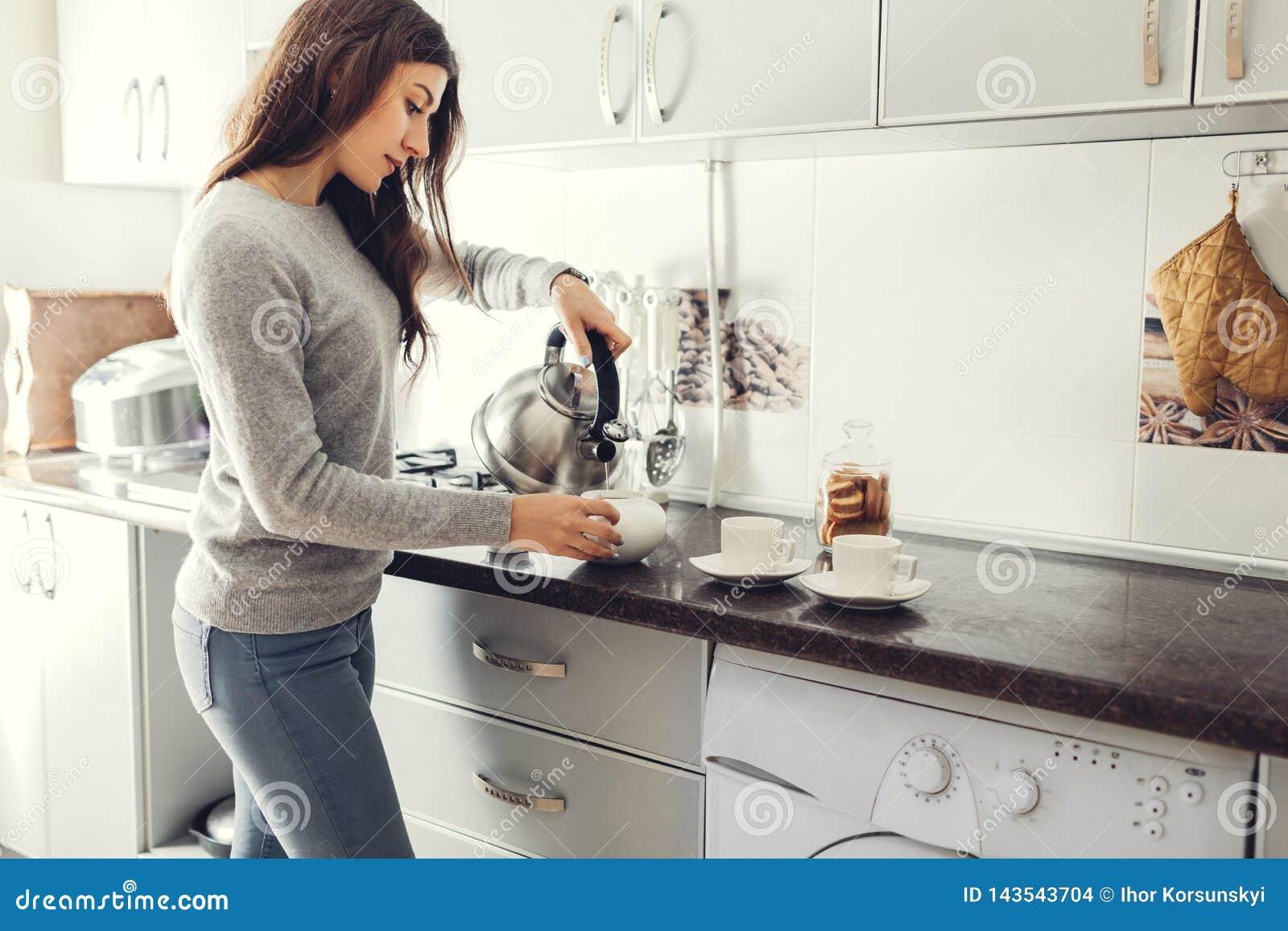 Thé se renversant de femme dans la tasse en céramique à la table