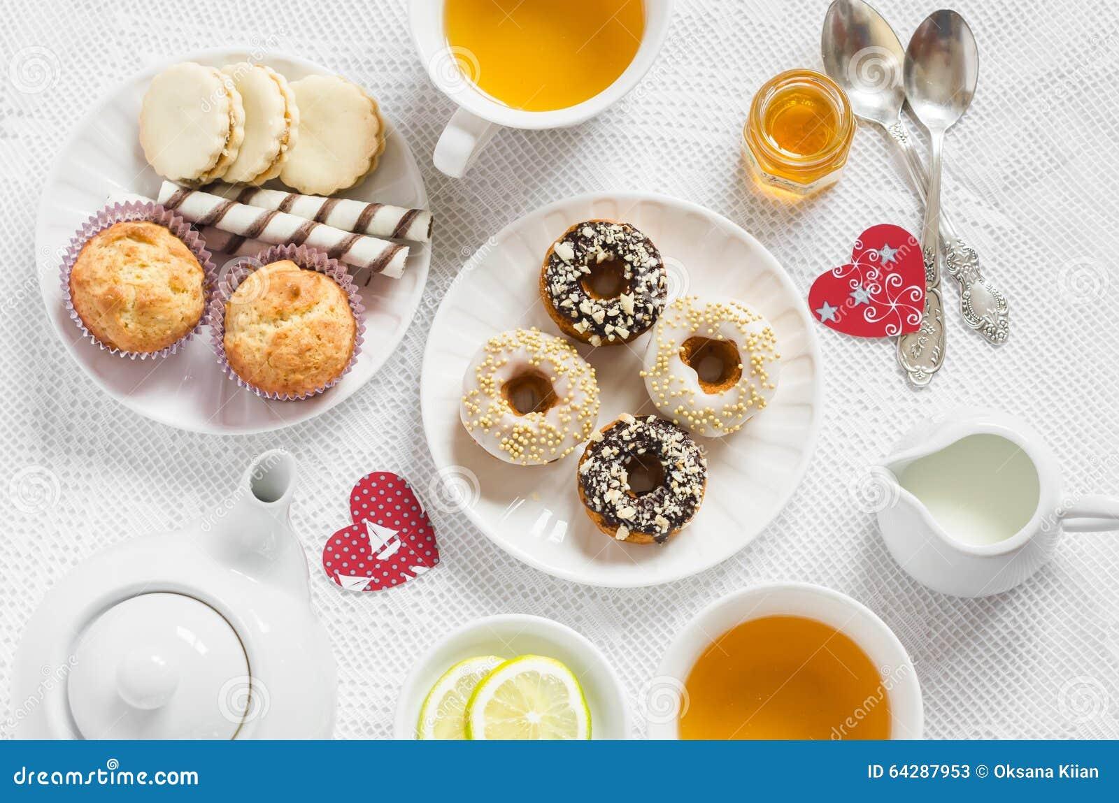 Thé vert de citron romantique de petit déjeuner de Saint-Valentin et bonbons - petits pains de banane, biscuits avec le caramel e