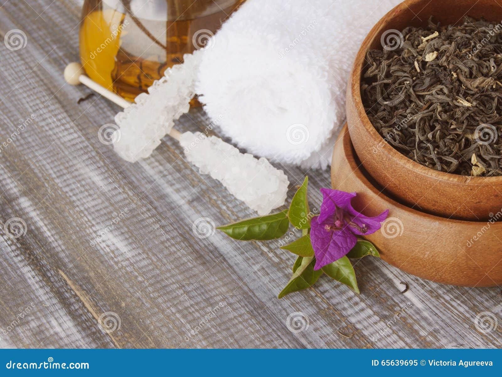 Thé vert de feuille dans la cuvette en bois avec du sucre sur le bâton