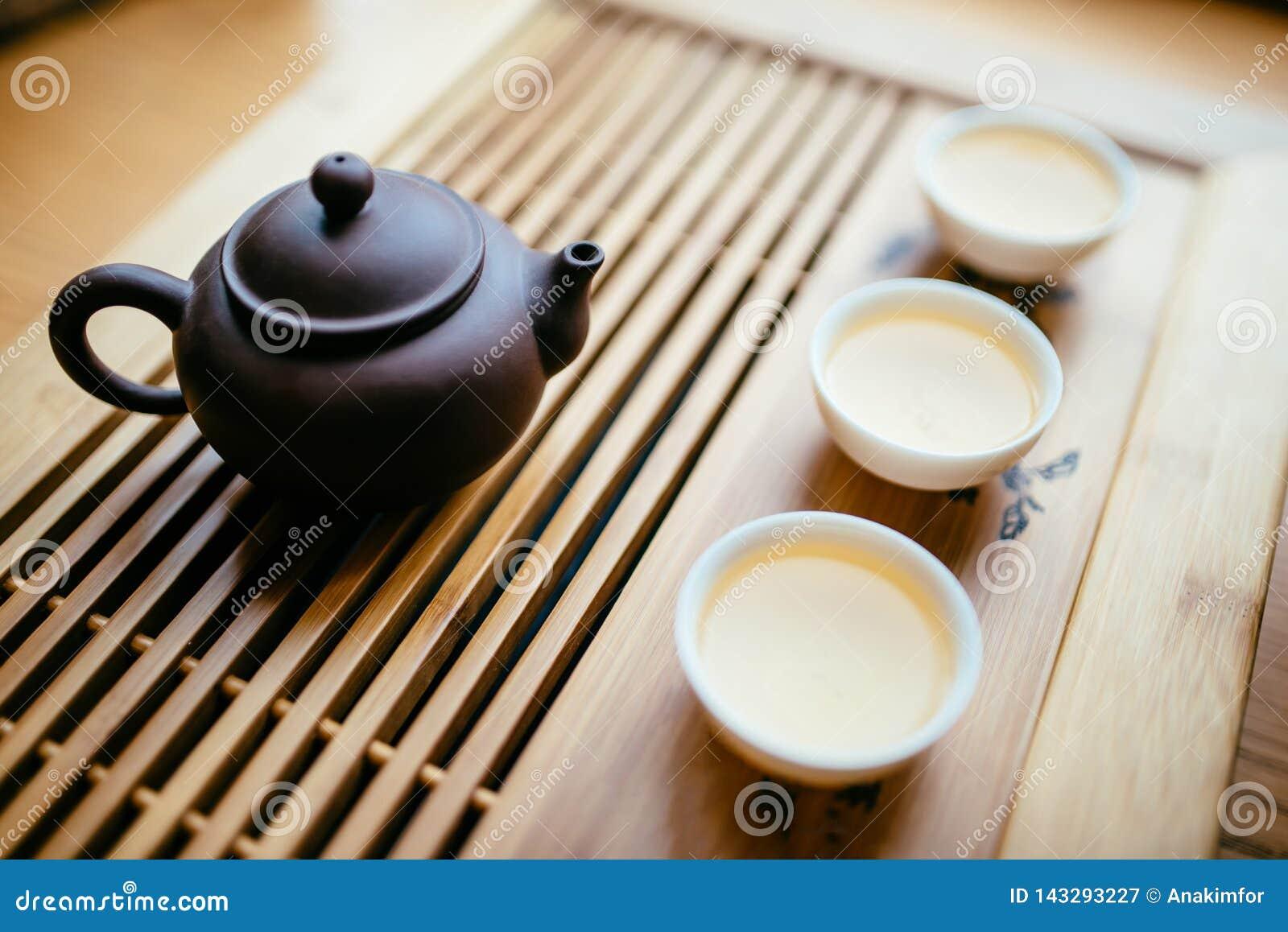 Théière et tasses avec le thé chinois sur la table pour la cérémonie de thé