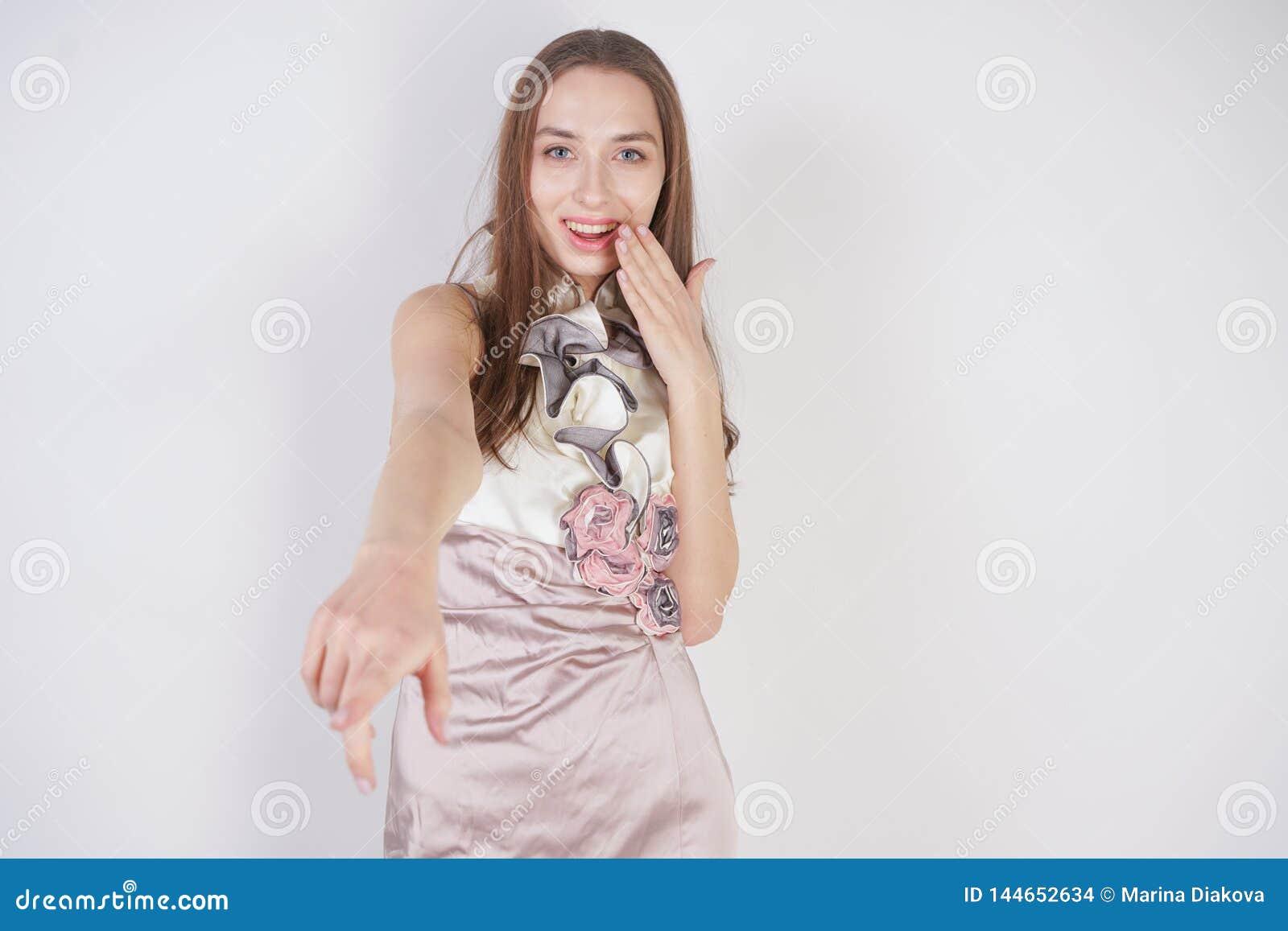Красивая кавказская предназначенная для подростков девушка стоит в коротком платье вечера и глумится собеседник, унижая, на белой