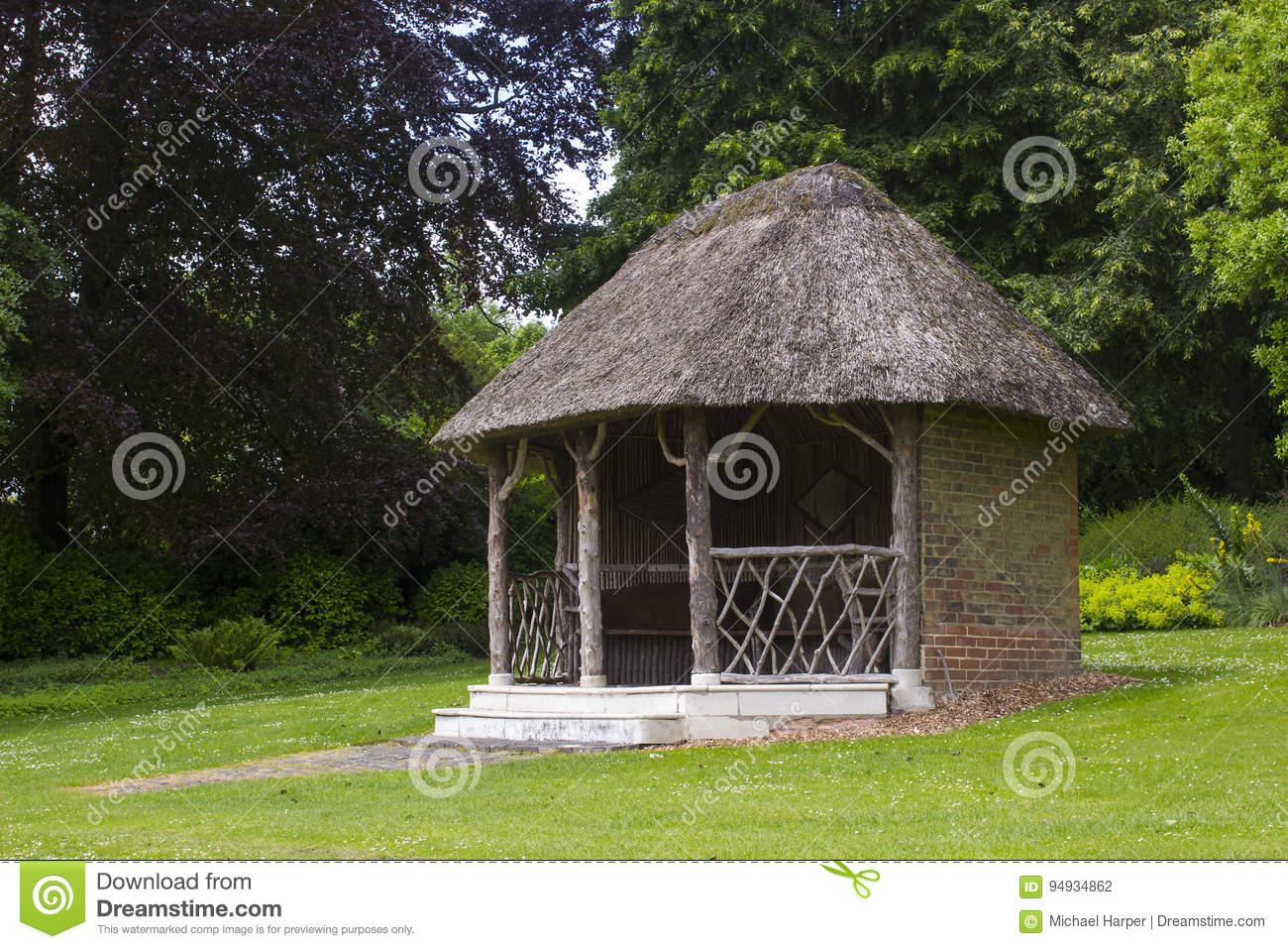 The 19th Century thatched summer house surrounded by beautiful flower beds and gravel paths in the walled garden at West Dean