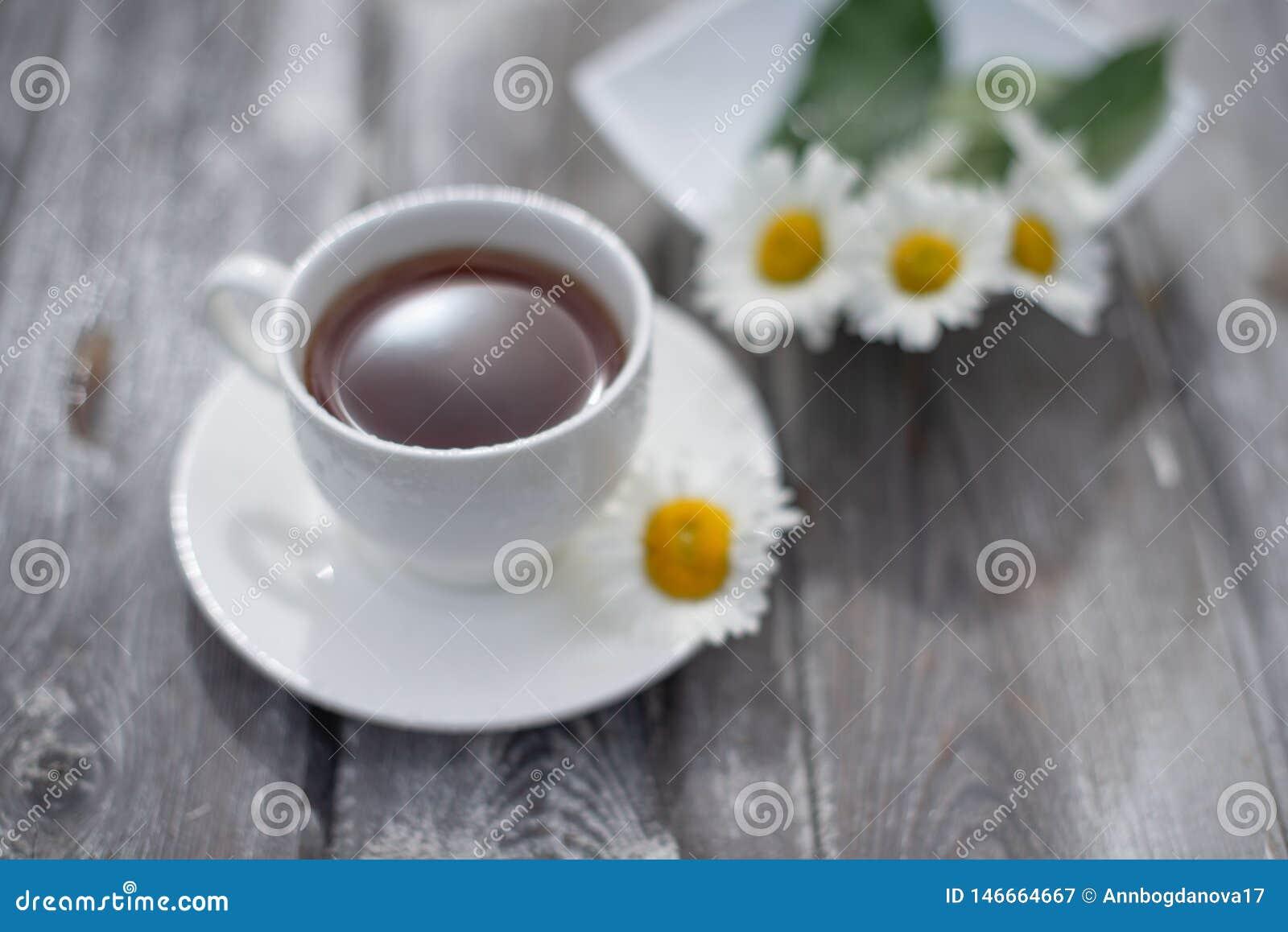 Th? dans une tasse blanche sur une table en bois Marguerites sur la table