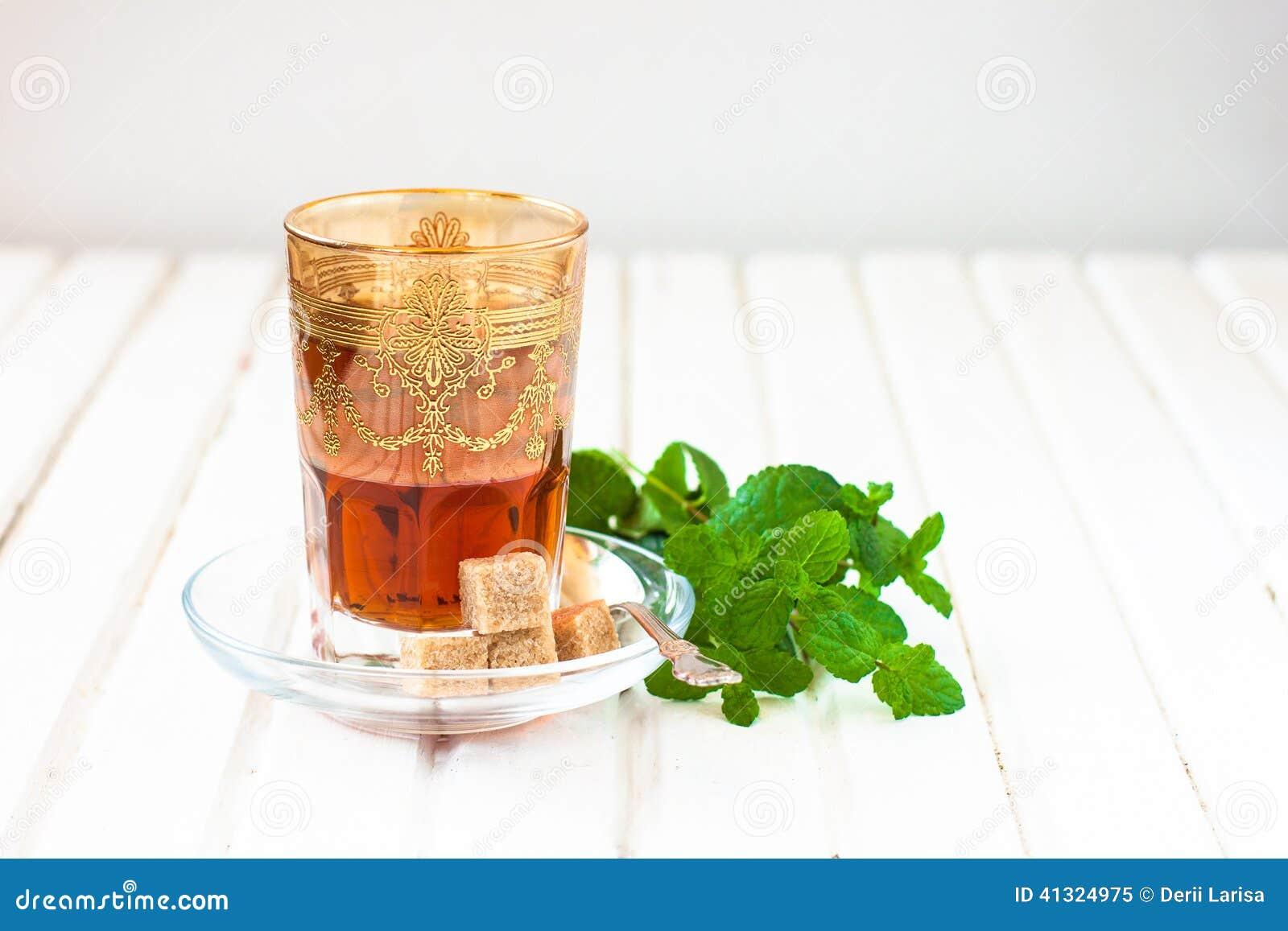 Th marocain avec la menthe et le sucre dans un verre sur for Position verre sur table