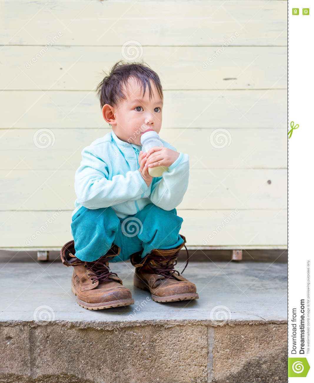 f4271d7bf Thai Baby boy try to wearing father's boots while drinking milk from bottle.