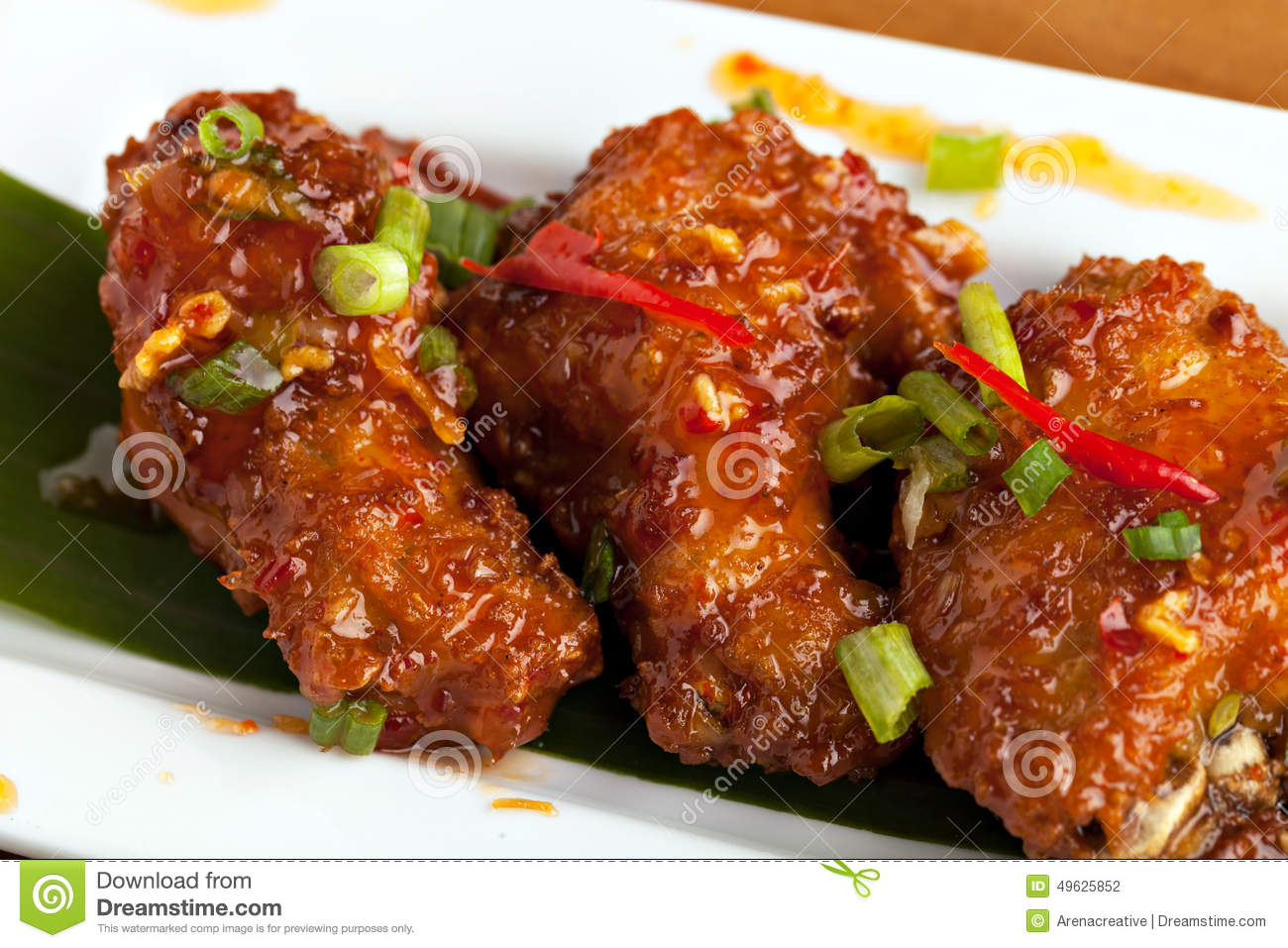 Thai style spicy chicken wings appetizer on a contemporary white plate ...