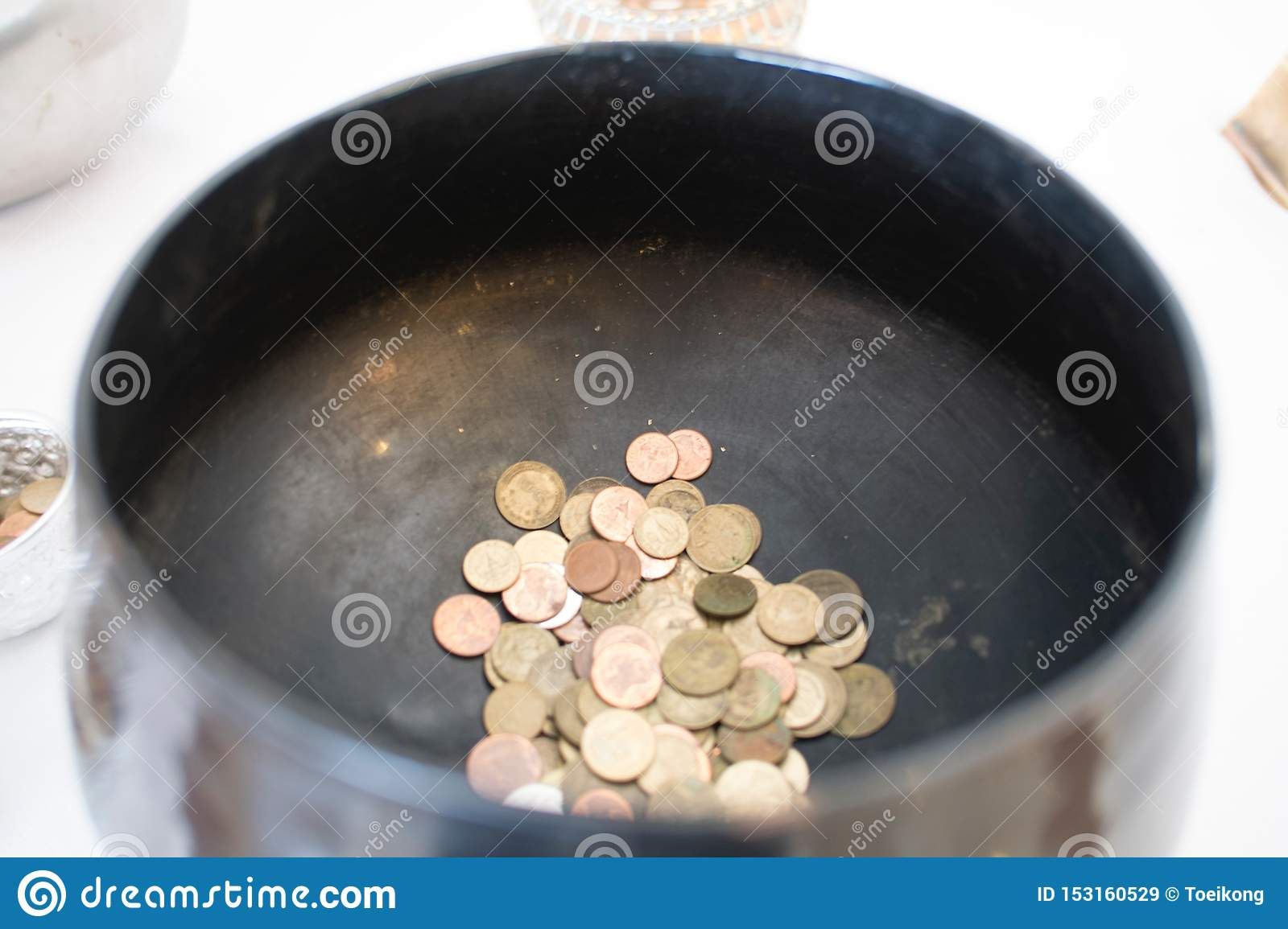 Thai coins in monk alms bowl