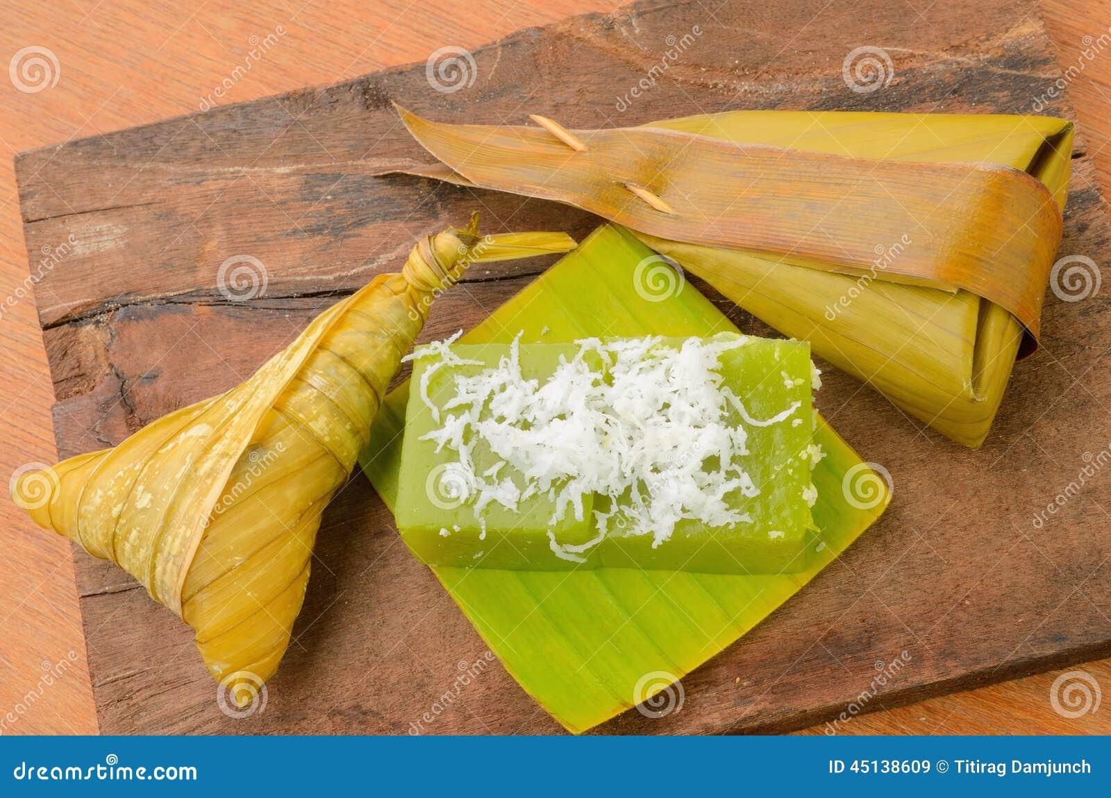 thai dessert sticky rice wrapped in banana leaf on wood. Black Bedroom Furniture Sets. Home Design Ideas