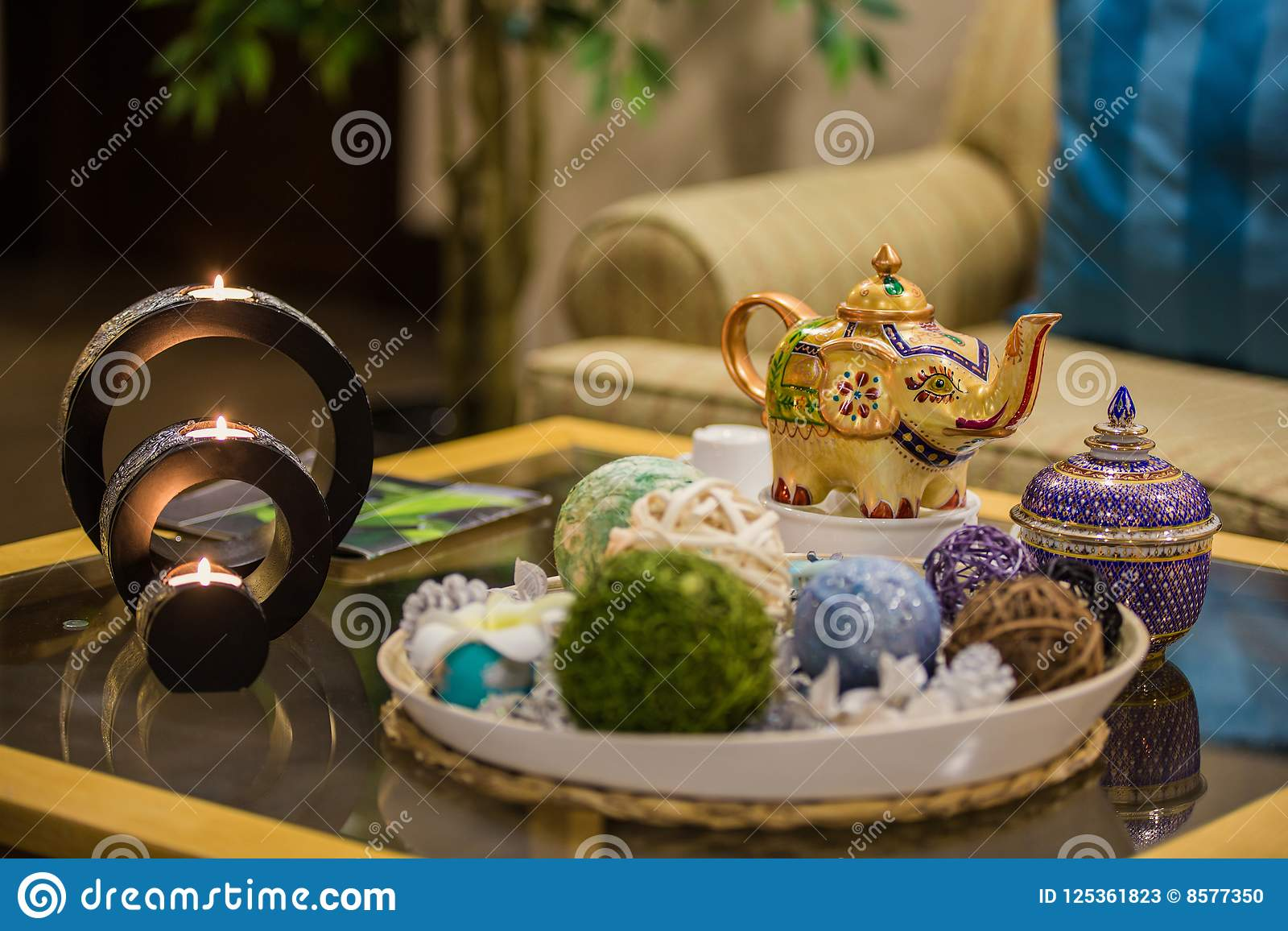 Thai interior details of spa, candles on table and kettle with tea