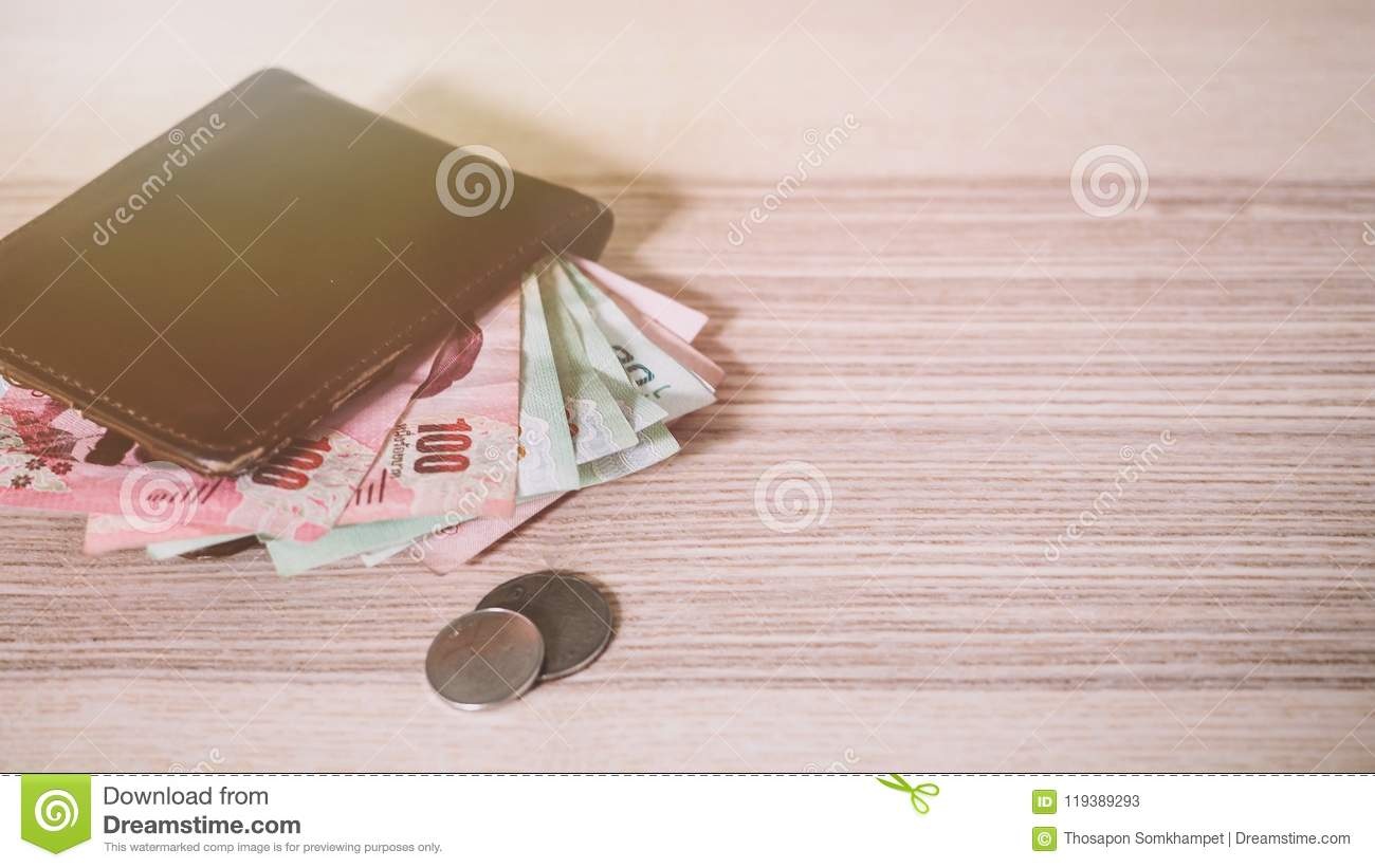 Thai money in the Brown wallet and Silver coin on wooden desk.