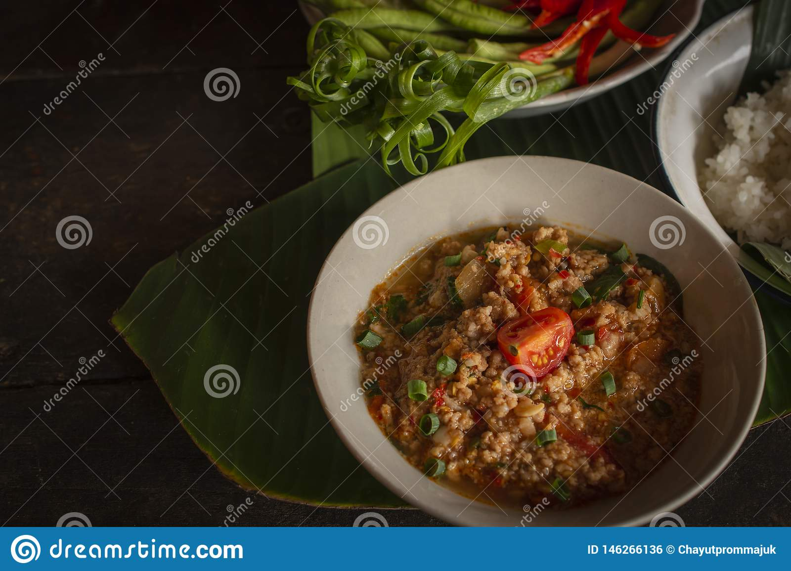 Thai Northern Style Pork and Tomato Chili Relish, nam prik ong in white bowl on wood table there are side dishes of fresh