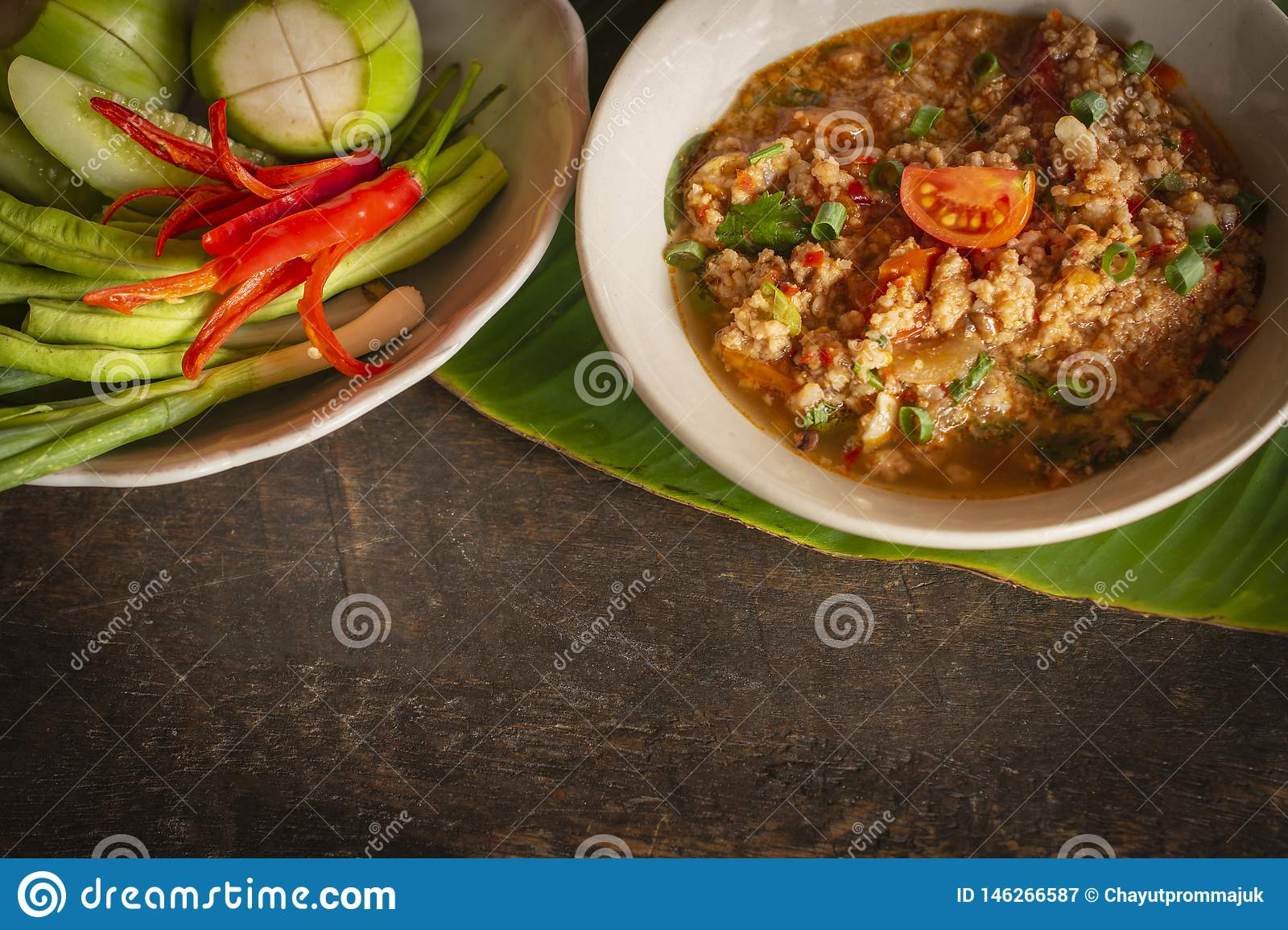 Thai Northern Style Pork and Tomato Chili Relish, nam prik ong in white bowl on wood table there is side dishes of fresh