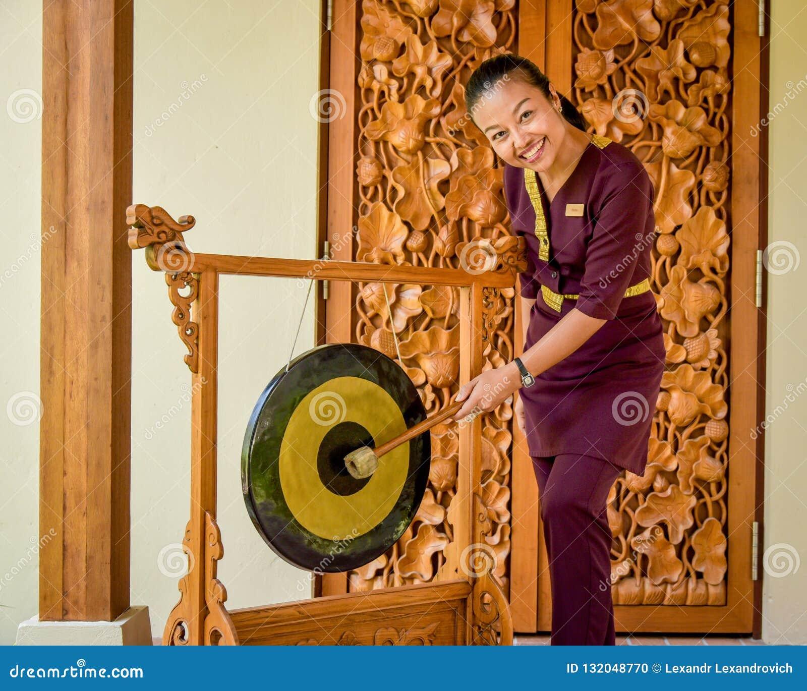 Thai restaurant waitress hitting the gong near entrance