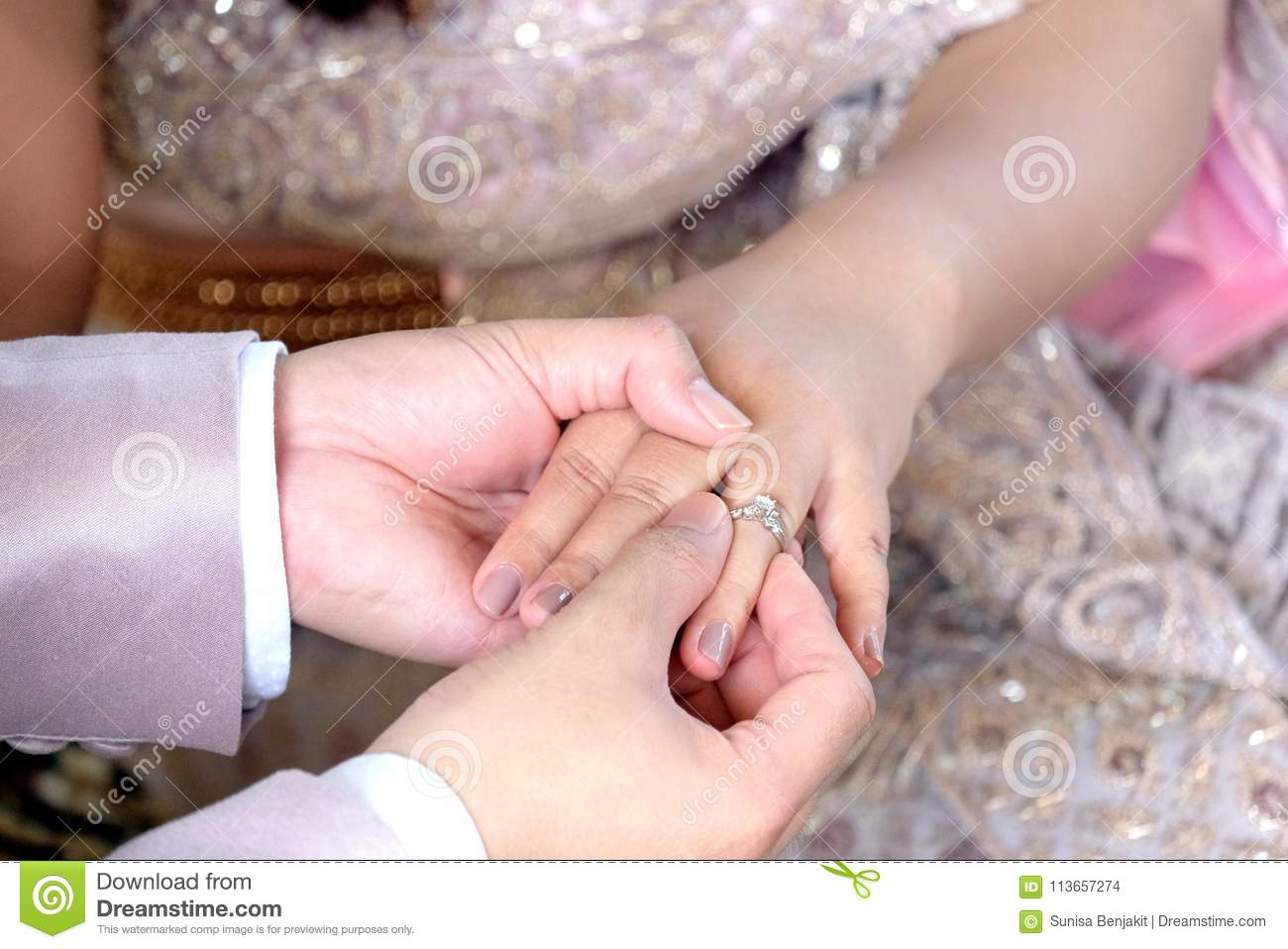 Thai Groom`s Hand Putting A Wedding Ring On The Bride`s Finger ...