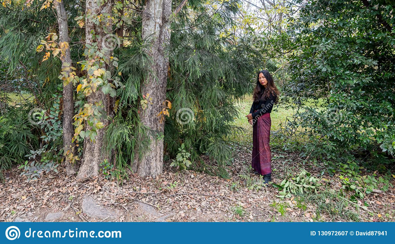 Thai woman standing in forest next to trees in sarong