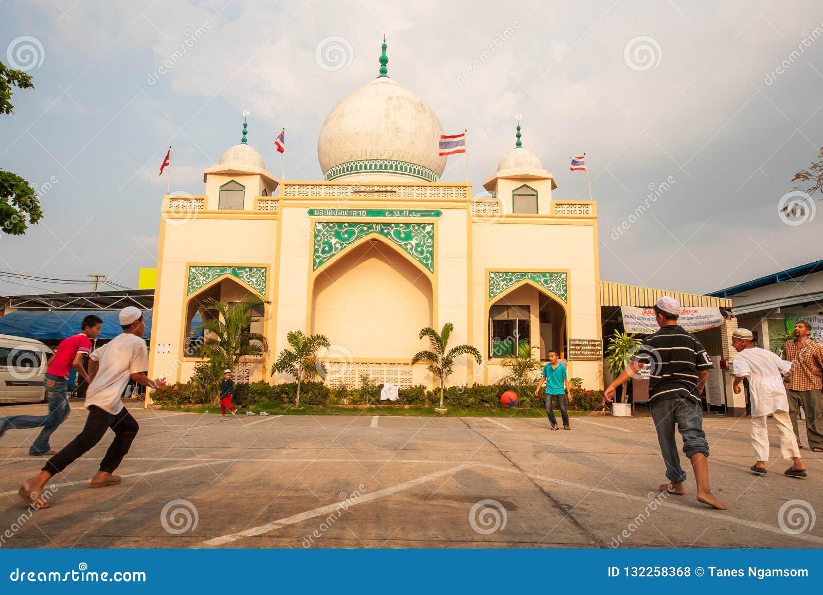 Thailändisch-Moslemjunge, der Fußballspiel vor alter Moschee spielt