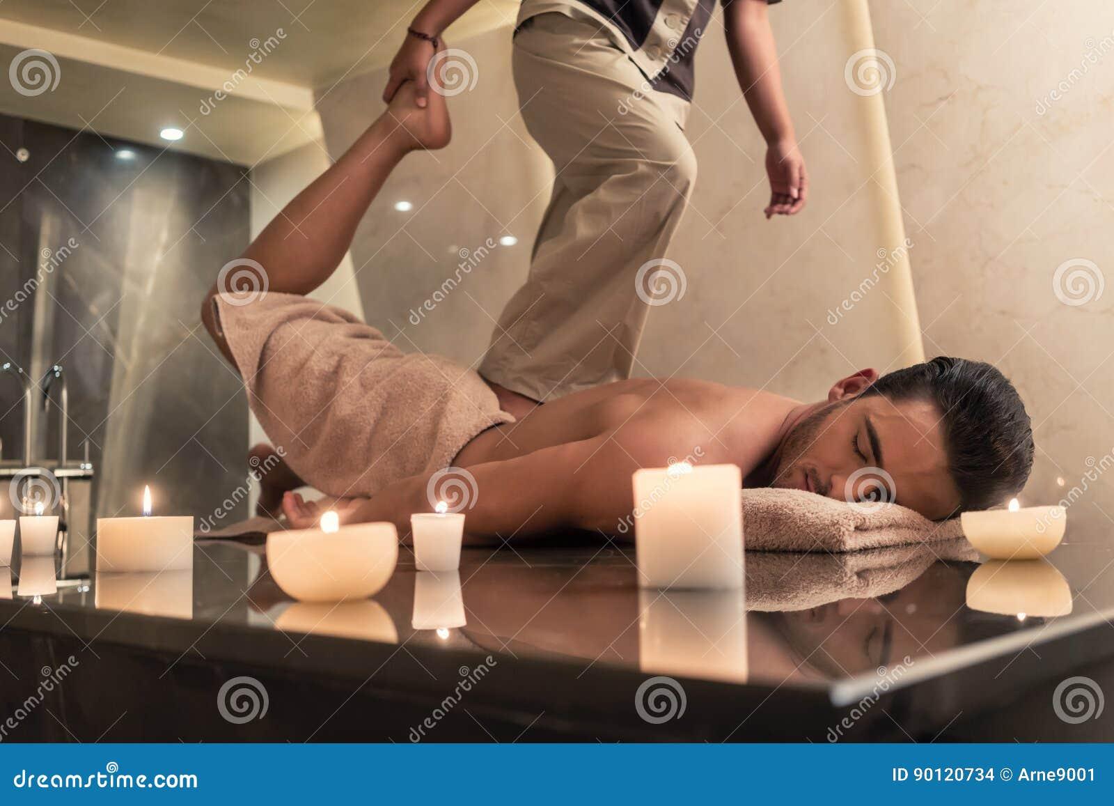 Thailändischer Massagepraktiker, der Mann durch das Ausdehnen von techn massiert