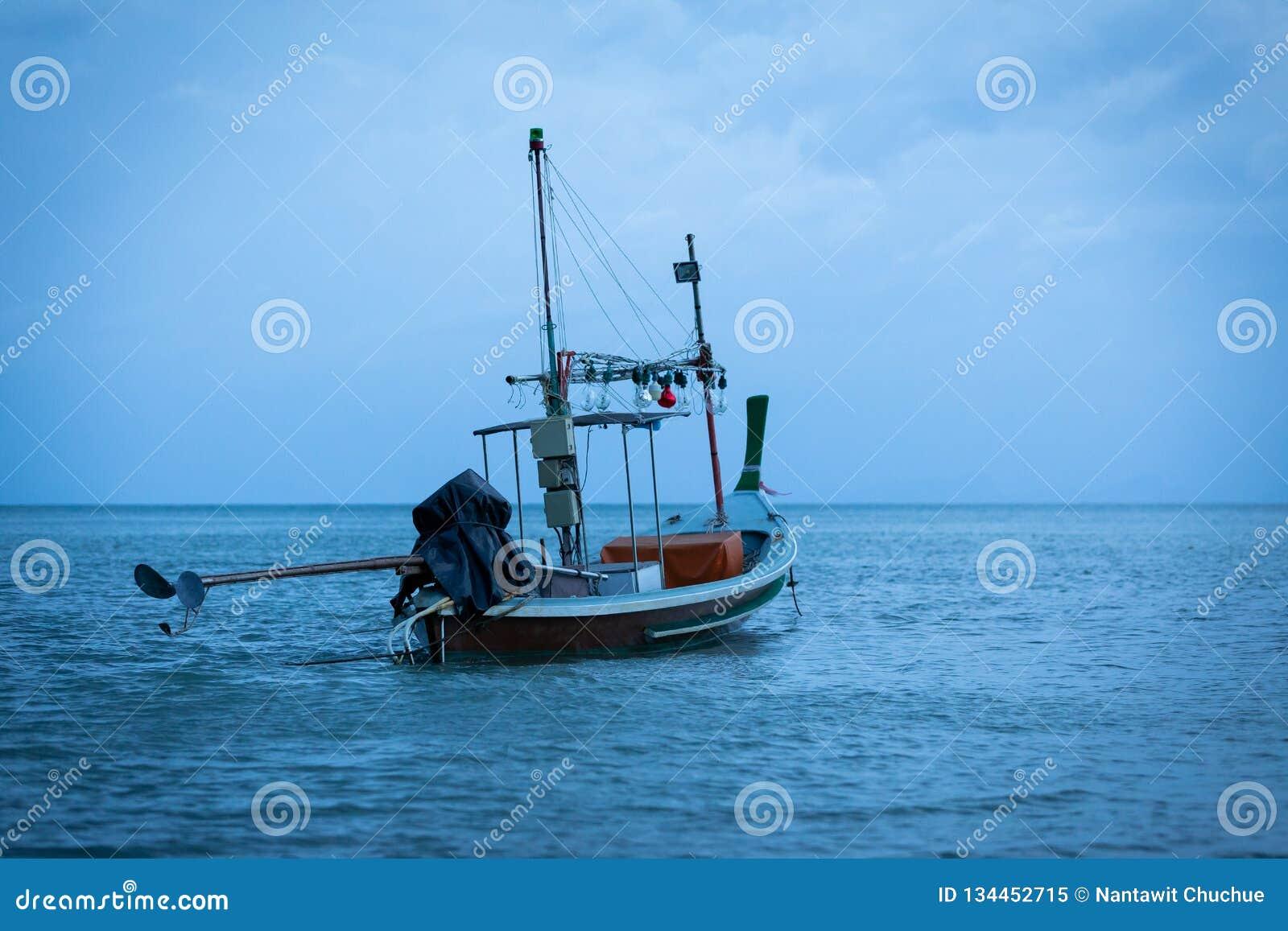 Thailändsk fiskebåt som parkeras i den blåa himlen för havsafton