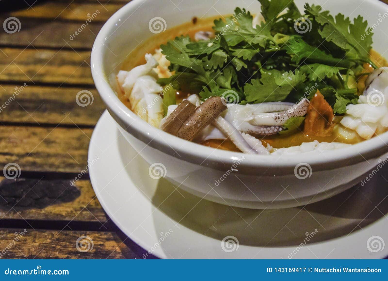 Thailändsk mat - kryddig soppagarnering för tioarmad bläckfisk med koriander i den vita bunken på träskrivbordet, läcker matställ