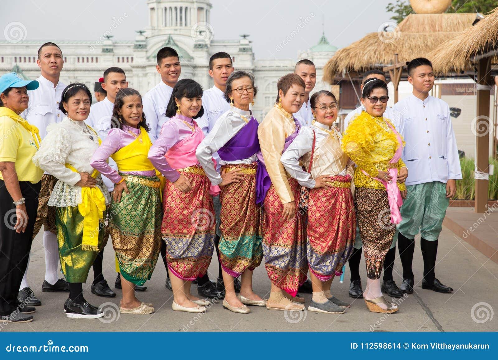 Thailändskt folk som bär den härliga nationella torkduken för traditionell stil för klänning