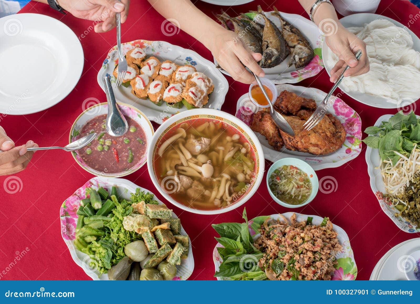 Thailändskt folk som tillsammans äter lokal thai mat