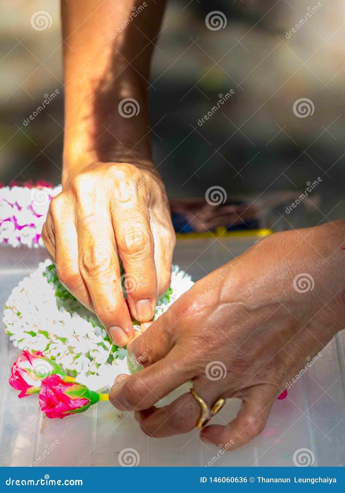 Thail?ndische Frau, die eine Tradition thail?ndische Blumengirlande herstellt