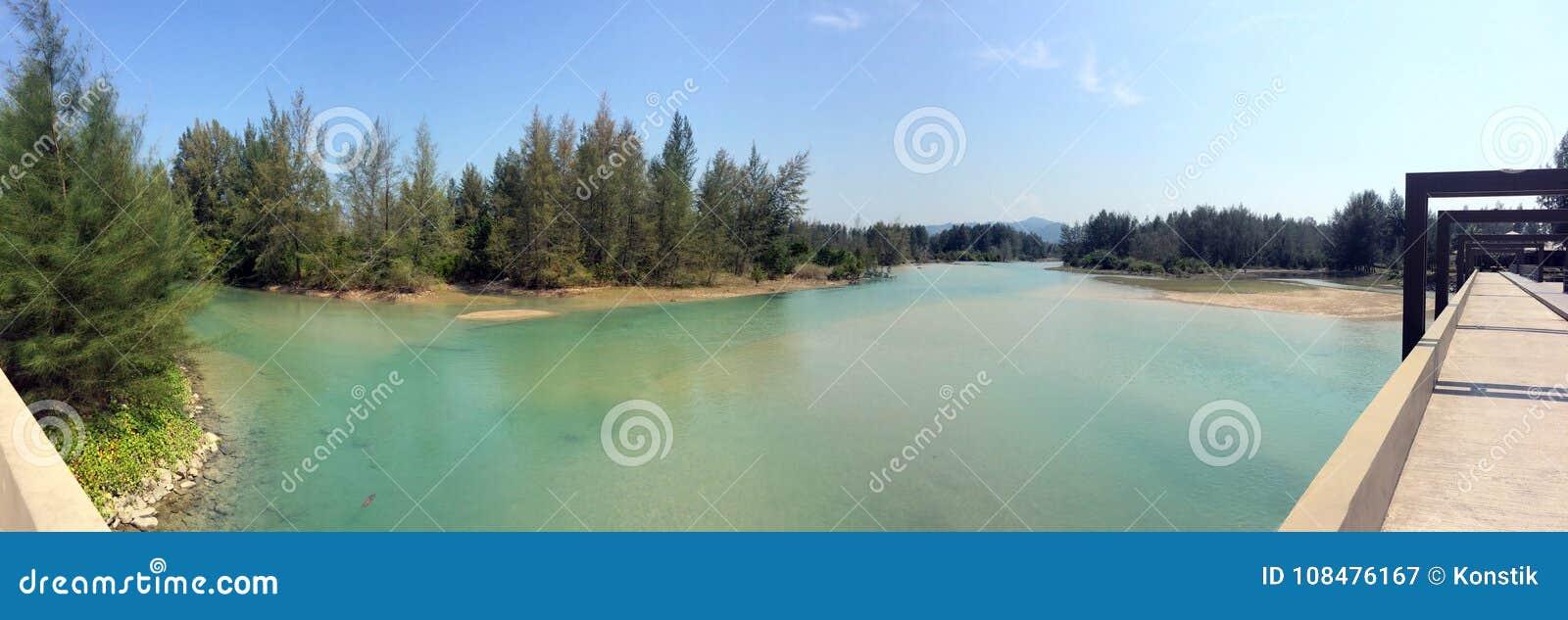 Thailand Bron över floden av floden som flödar in i havet under tillflöde och den sandiga stranden med barrträd