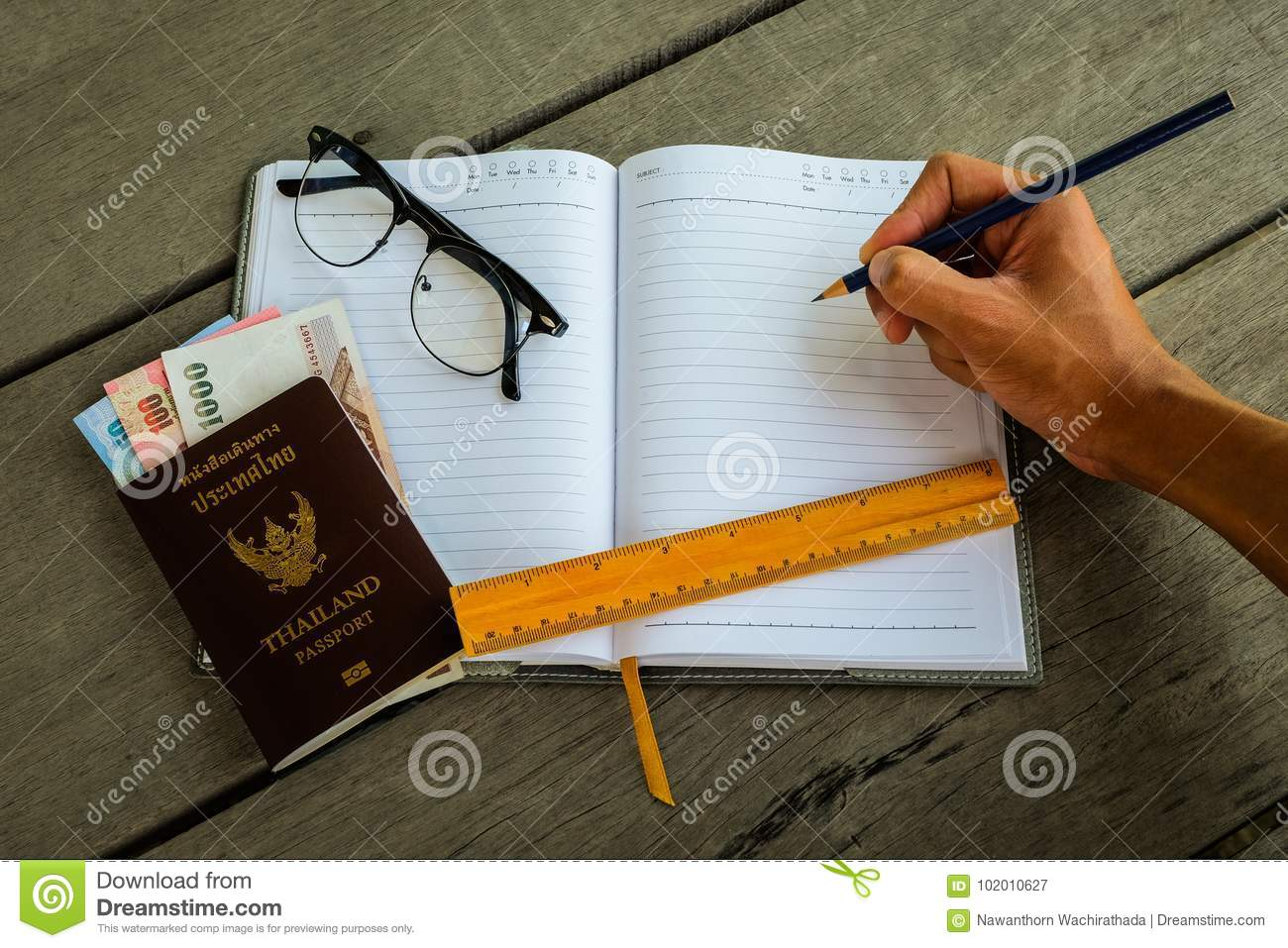 Thailand passport with money, yellow ruler, hand with pencil
